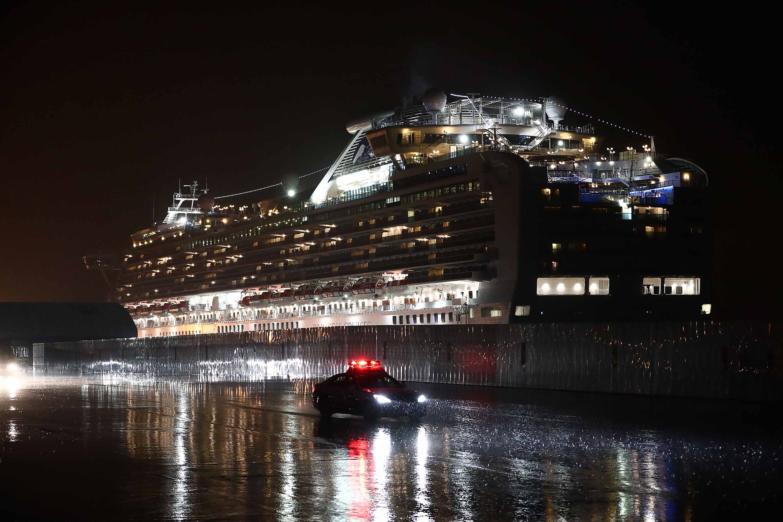 A police car drives past the Diamond Princess cruise ship at Yokohama port on Sunday.