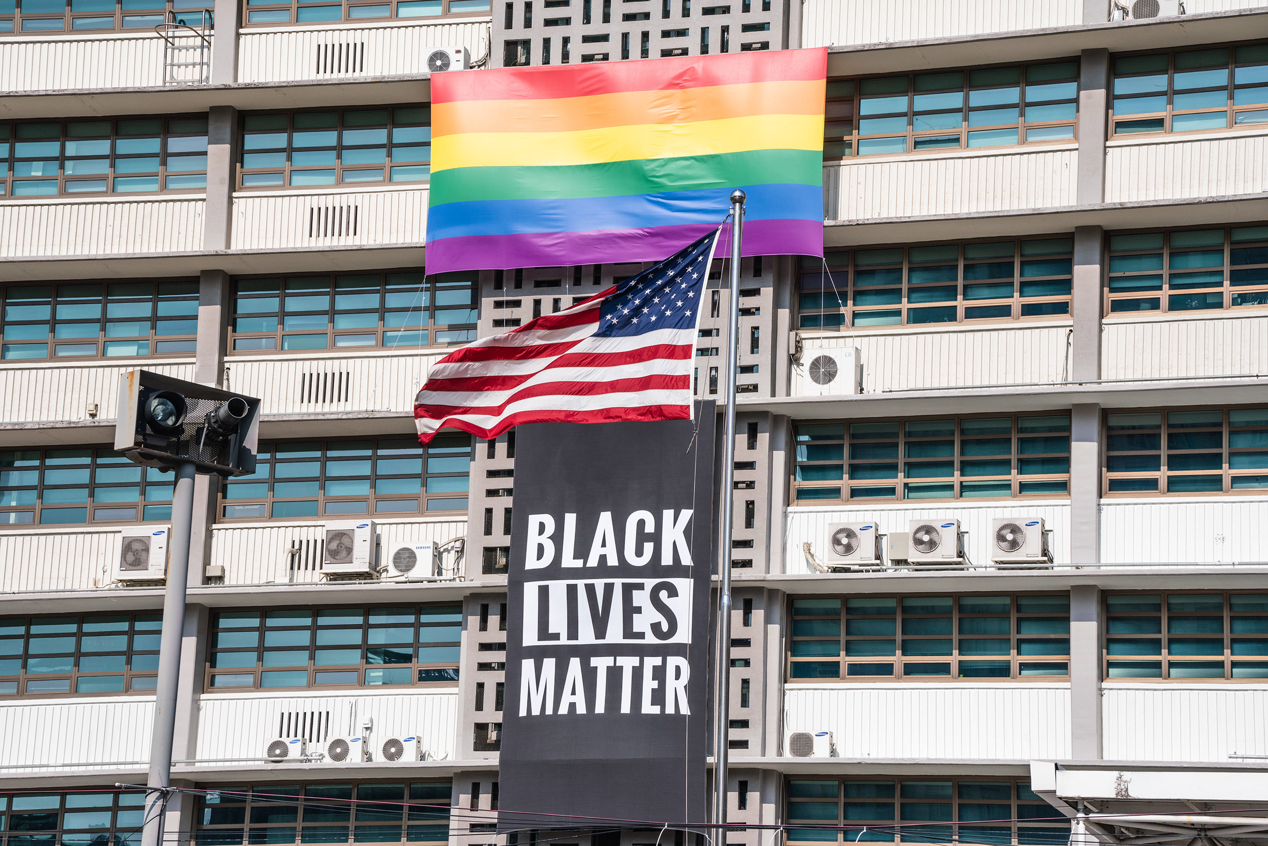 A Black Lives Matter banner, a United States national flag and a rainbow flag are hung on the facade of the US embassy building in Seoul, Korea, on Sunday, June 14.
