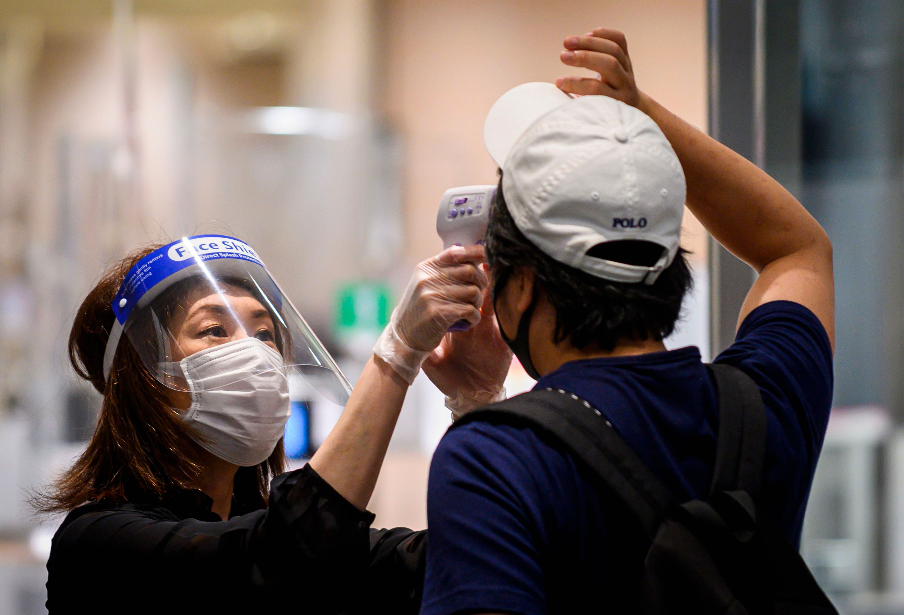 An employee conducts a temperature check on a customer at the entrance of the Shibuya Hikarie building on May 26 in Tokyo, Japan.