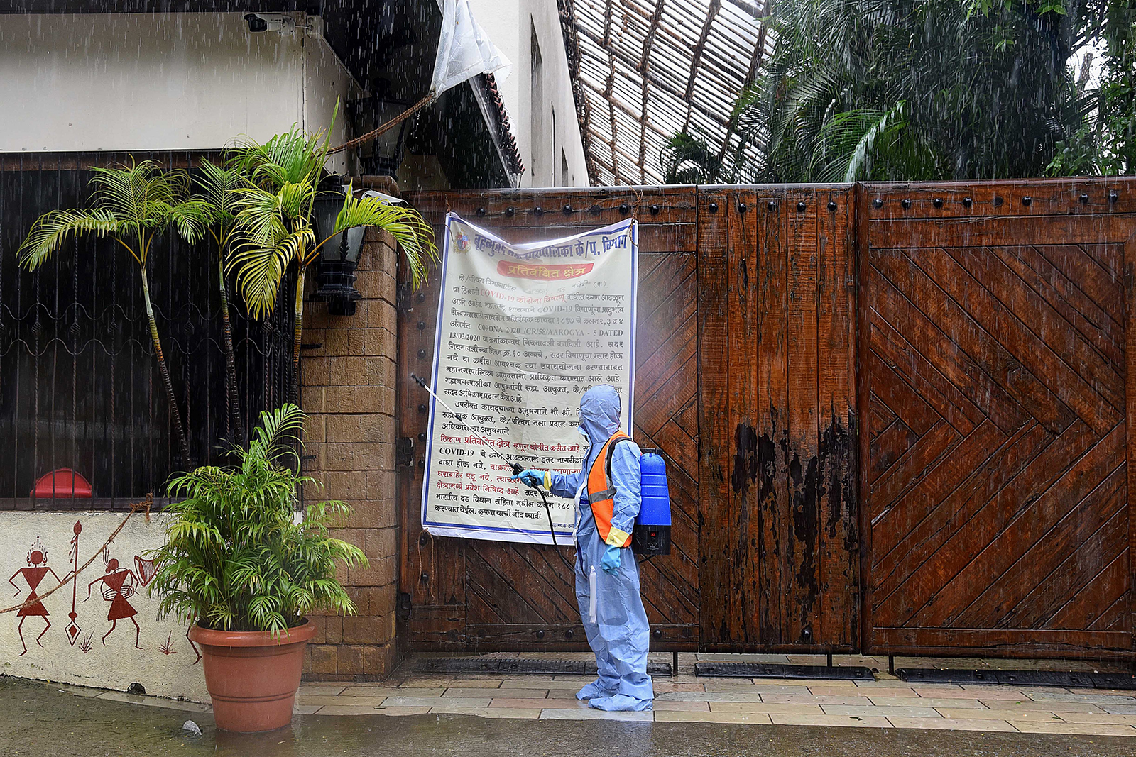 A civic authority worker sprays sanitizer on the main door of the residence of Bollywood star Amitabh Bachchan as he tested positive for COVID-19 in Mumbai on July 12.