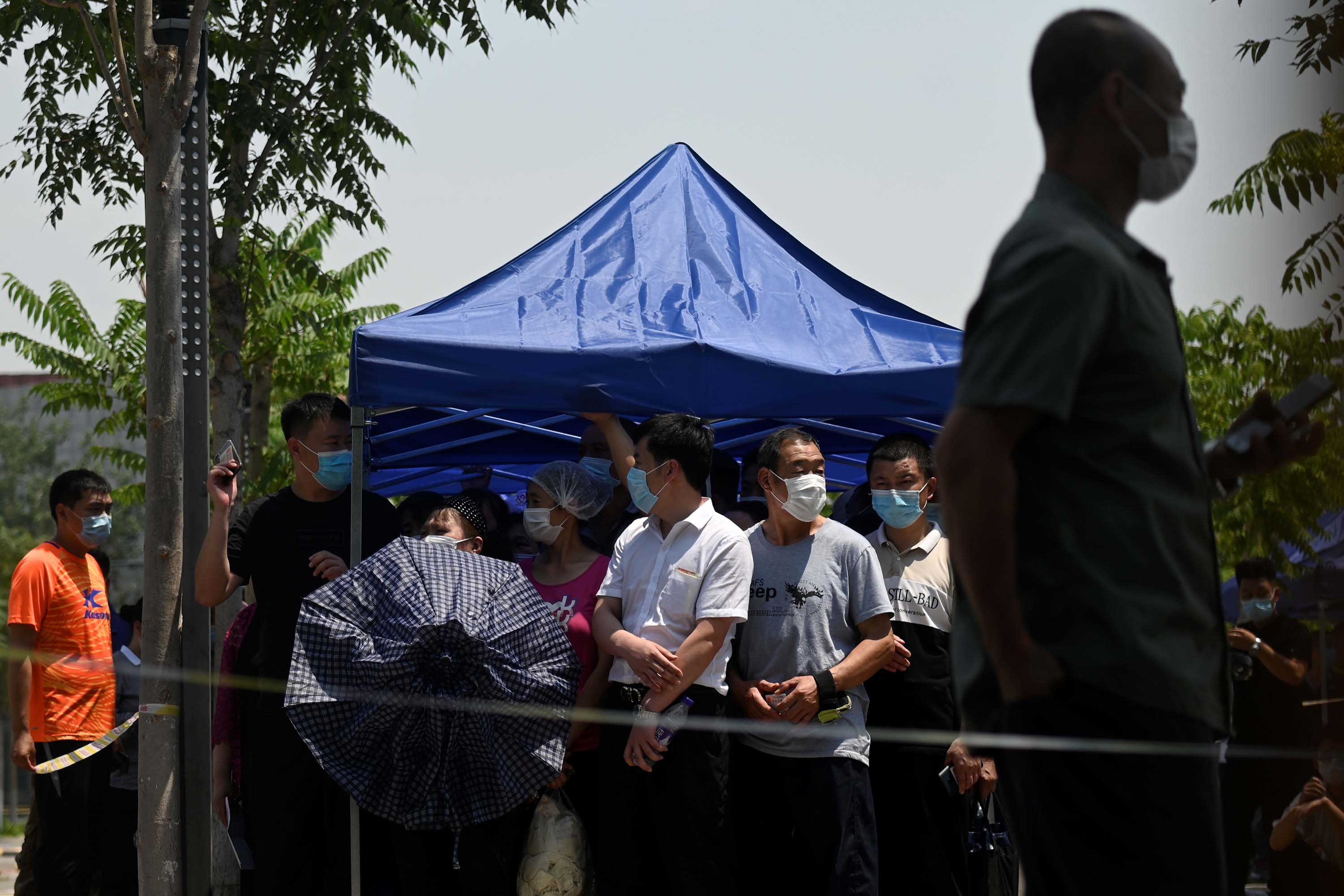 People wait to take a swab for COVID-19 at a testing site in Beijing on June 18.