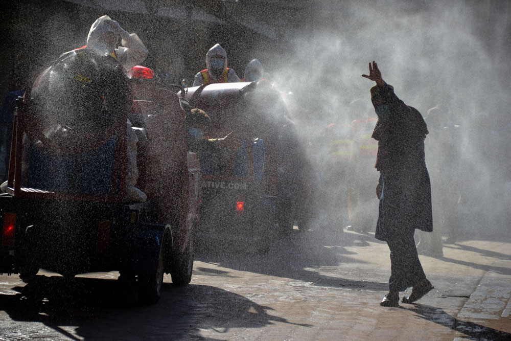 Rescue workers spray disinfectant along a road in Peshawar on May 6.