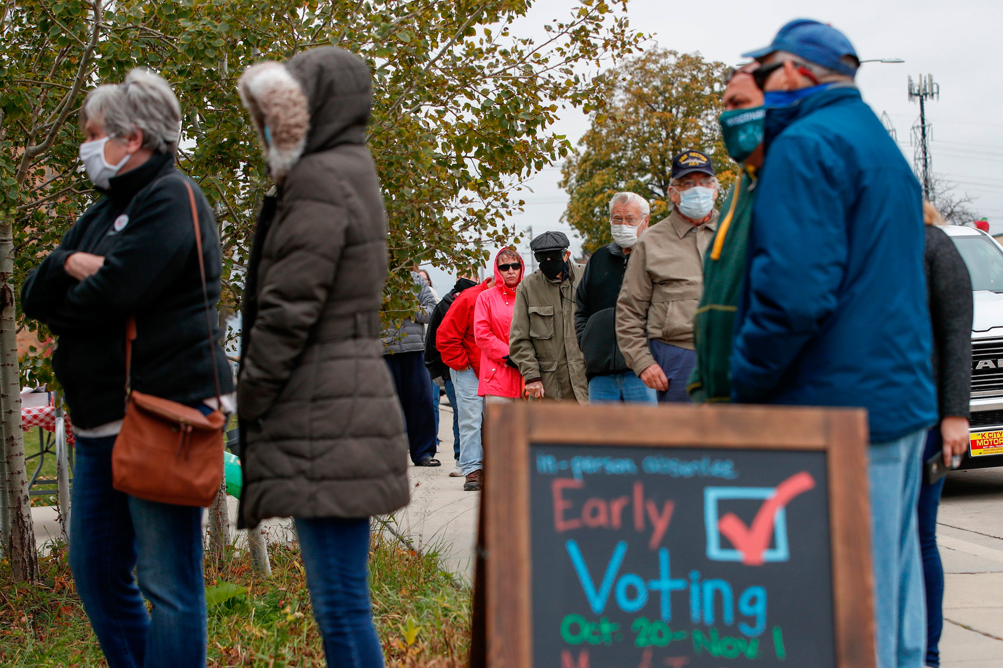 People wait in line to cast their ballots outside Tippecanoe Library in Milwaukee, Wisconsin, on October 20.
