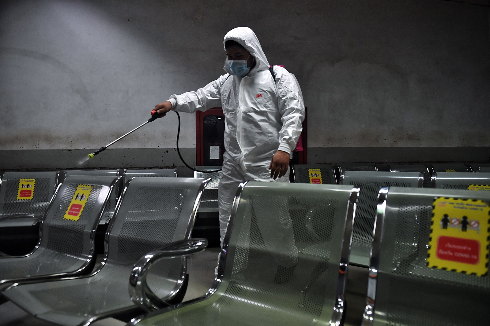 A man sprays disinfectant on seats inside a waiting room at Mo Chit Bus Terminal in Bangkok on January 6.