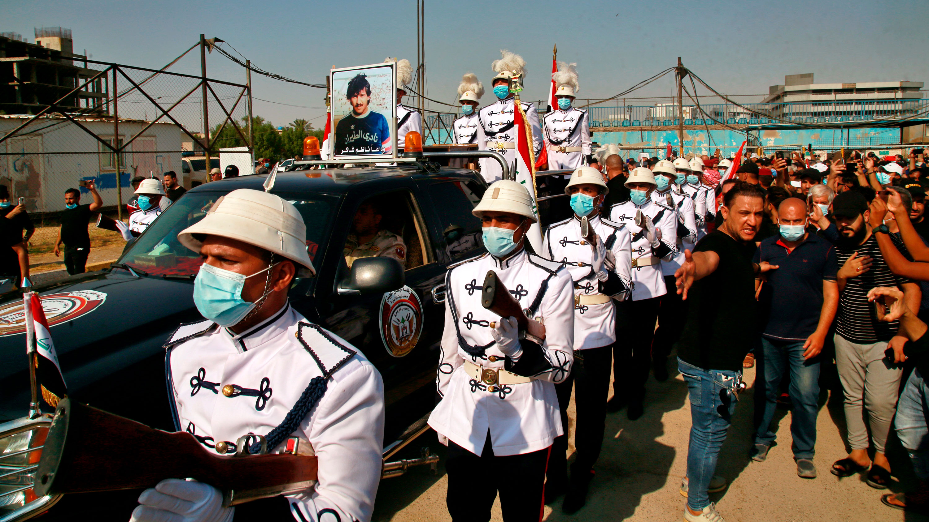 A military band and soccer fans escort the coffin of former Iraqi soccer star Nadhim Shaker during his funeral procession in Baghdad, Iraq, on September 12.