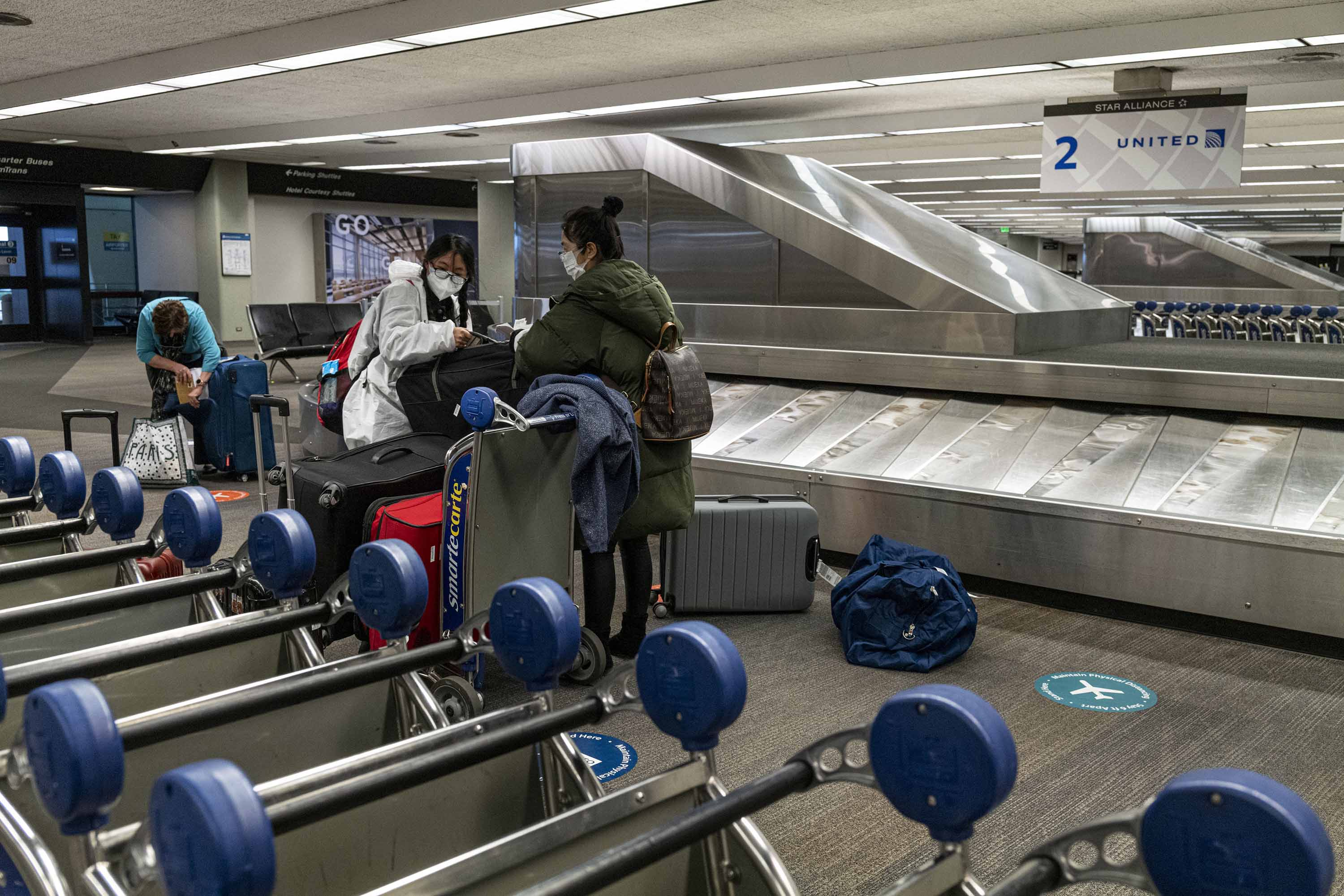 Travelers load baggage onto a cart at San Francisco International Airport on January 19.