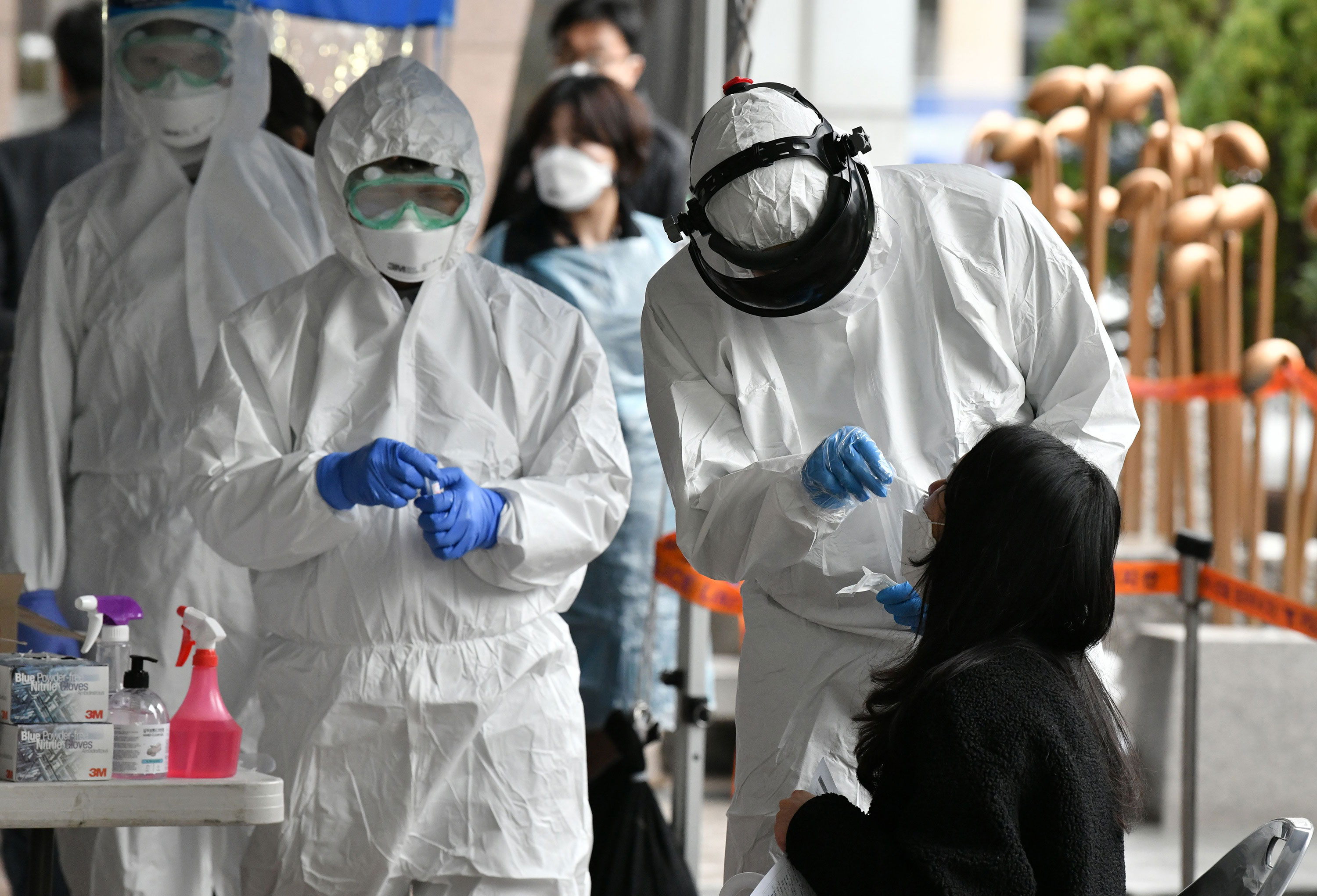 Medical staff take samples from workers at a building where multiple people were confirmed to have coronavirus in Seoul, South Korea on March 10.