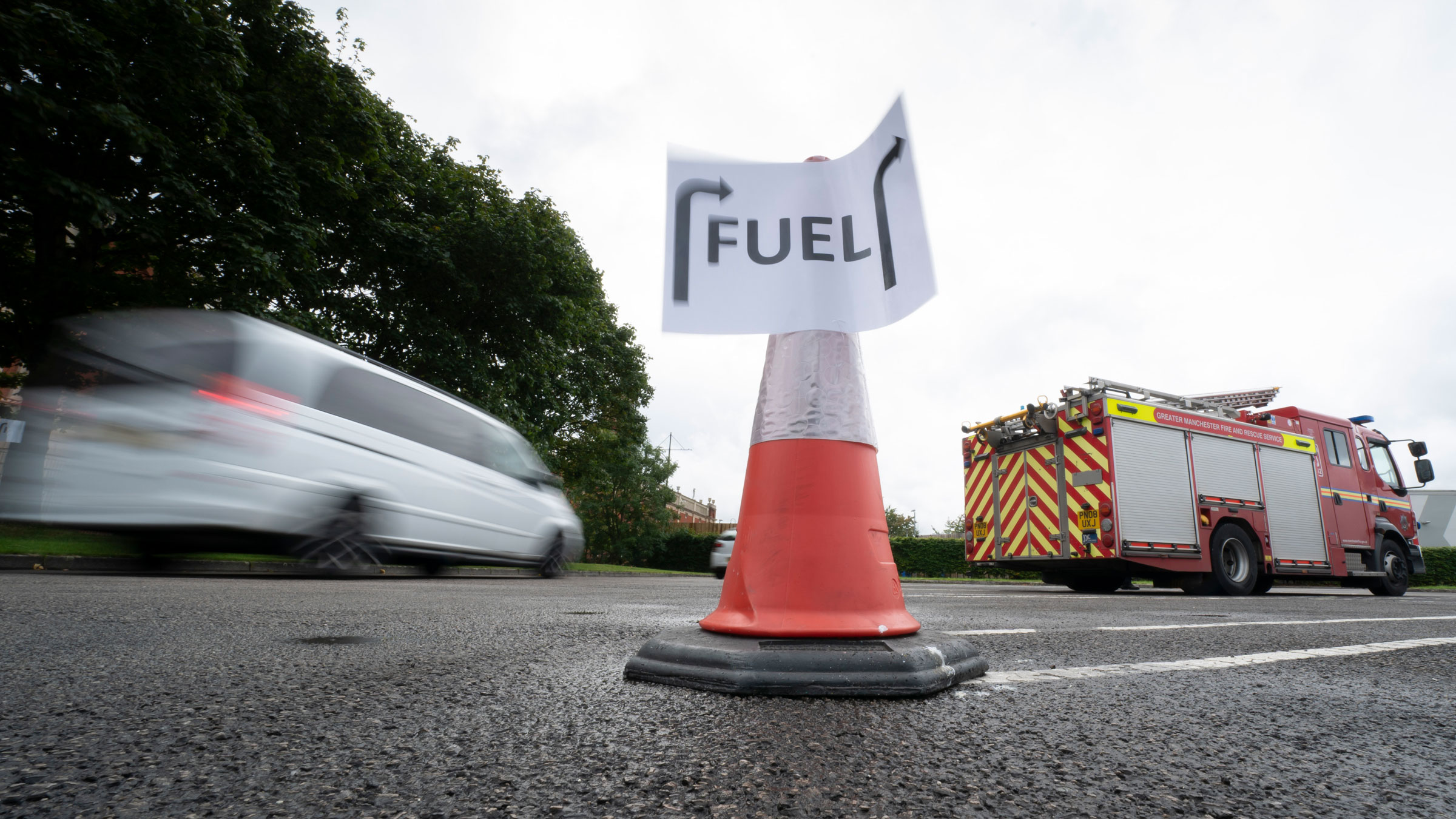 Vehicles arrive at a gas station in Manchester, England, on Tuesday.