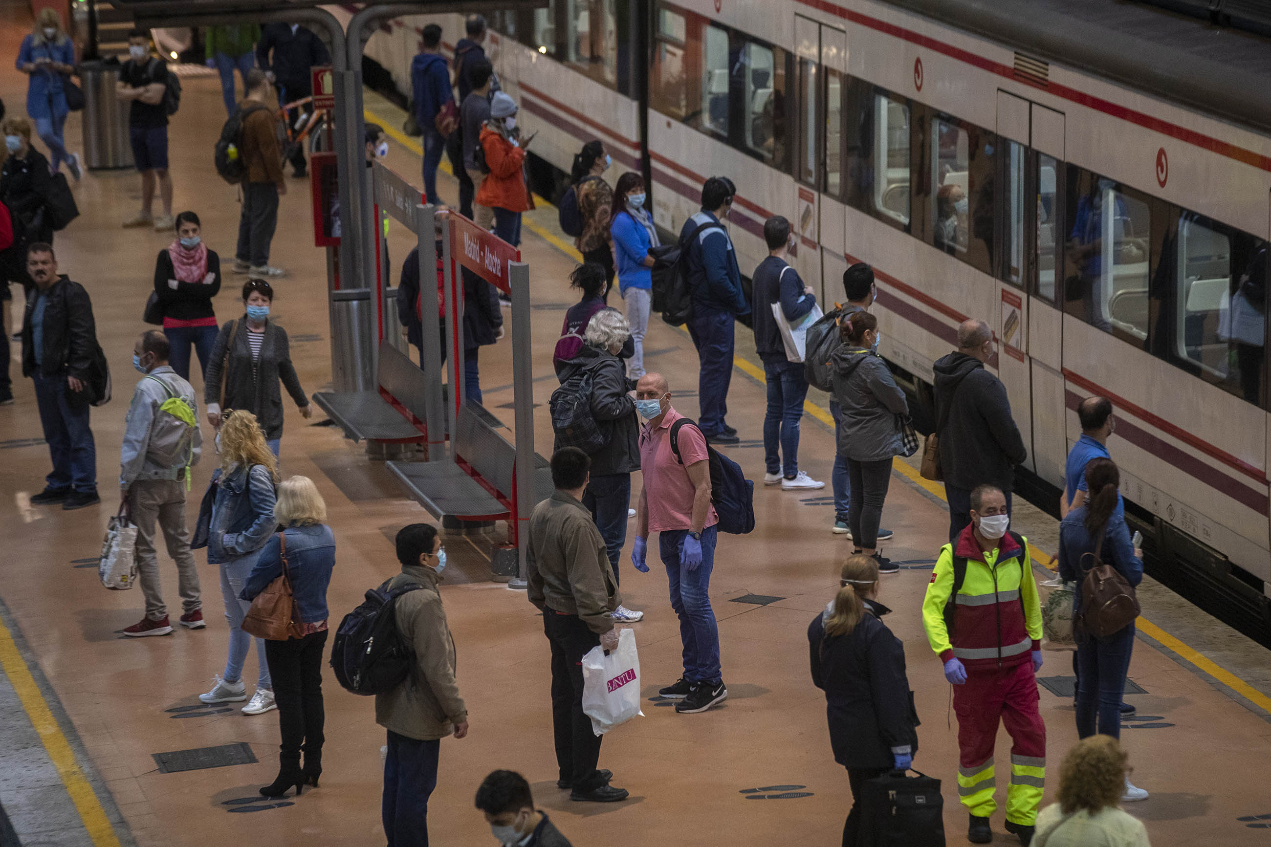 Commuters wear face masks to protect against coronavirus on a platform at Atocha train station in Madrid, Spain, on Monday, May 4.