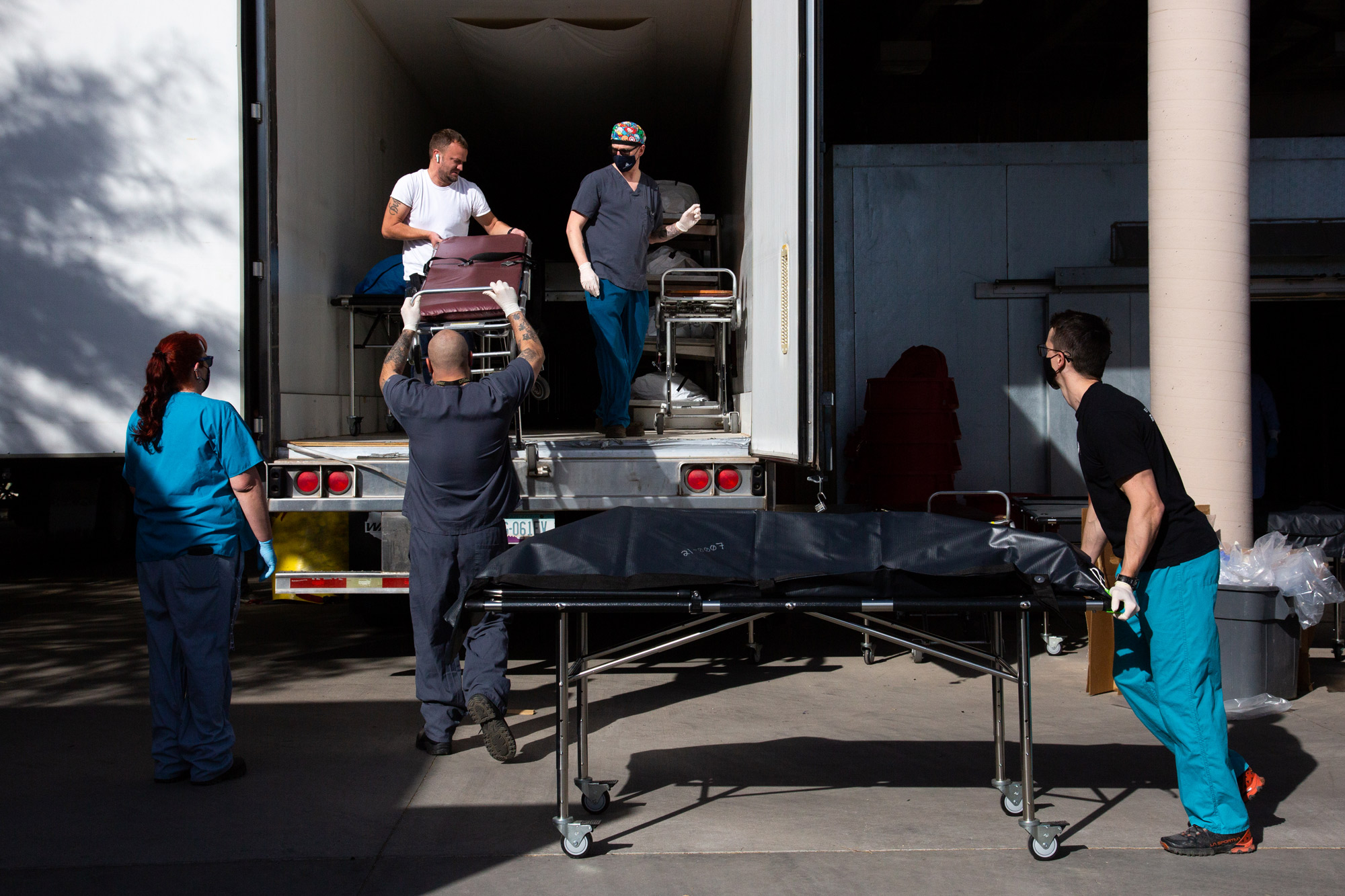 Employees move bodies into refrigerated semi-trucks at the Pima County Office of the Medical Examiner on January 14 in Tucson, Arizona.