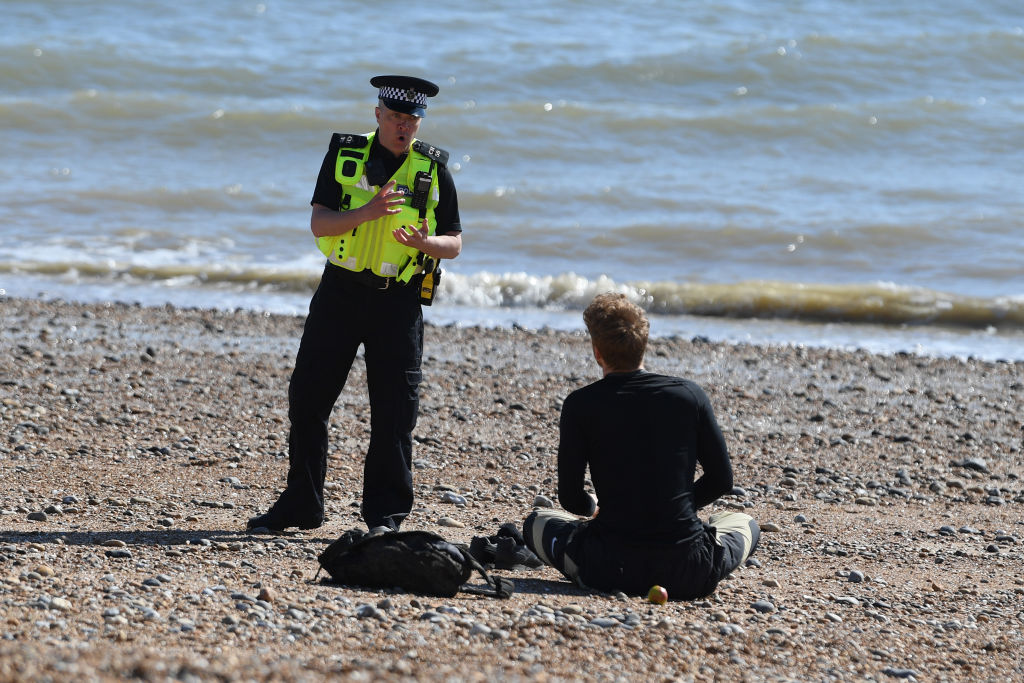 A police officer moves a sunbather off a beach in Brighton, southern England.