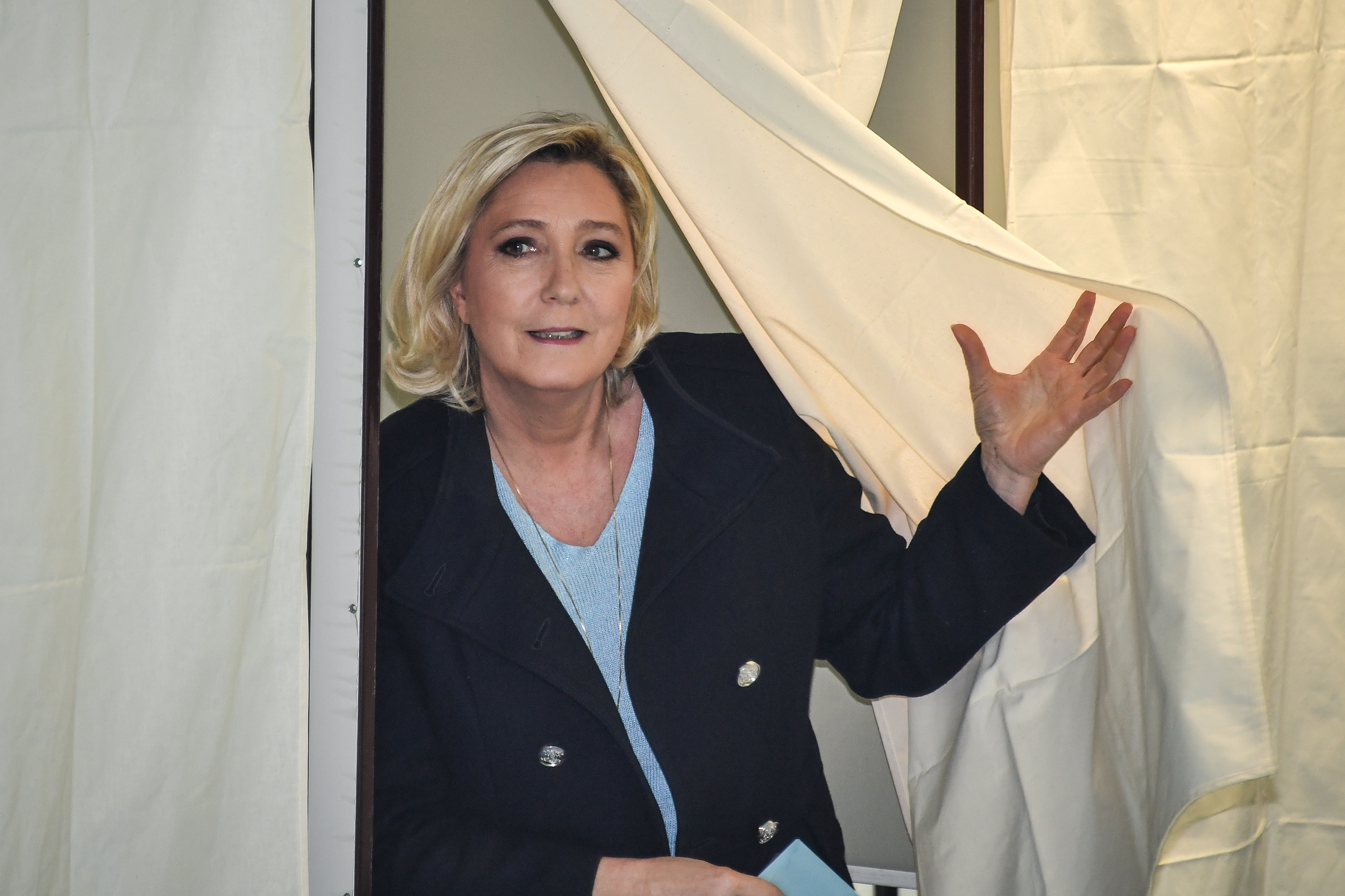 French far-right National Rally president Le Pen leaves the polling booth to cast her vote for the European Parliament.