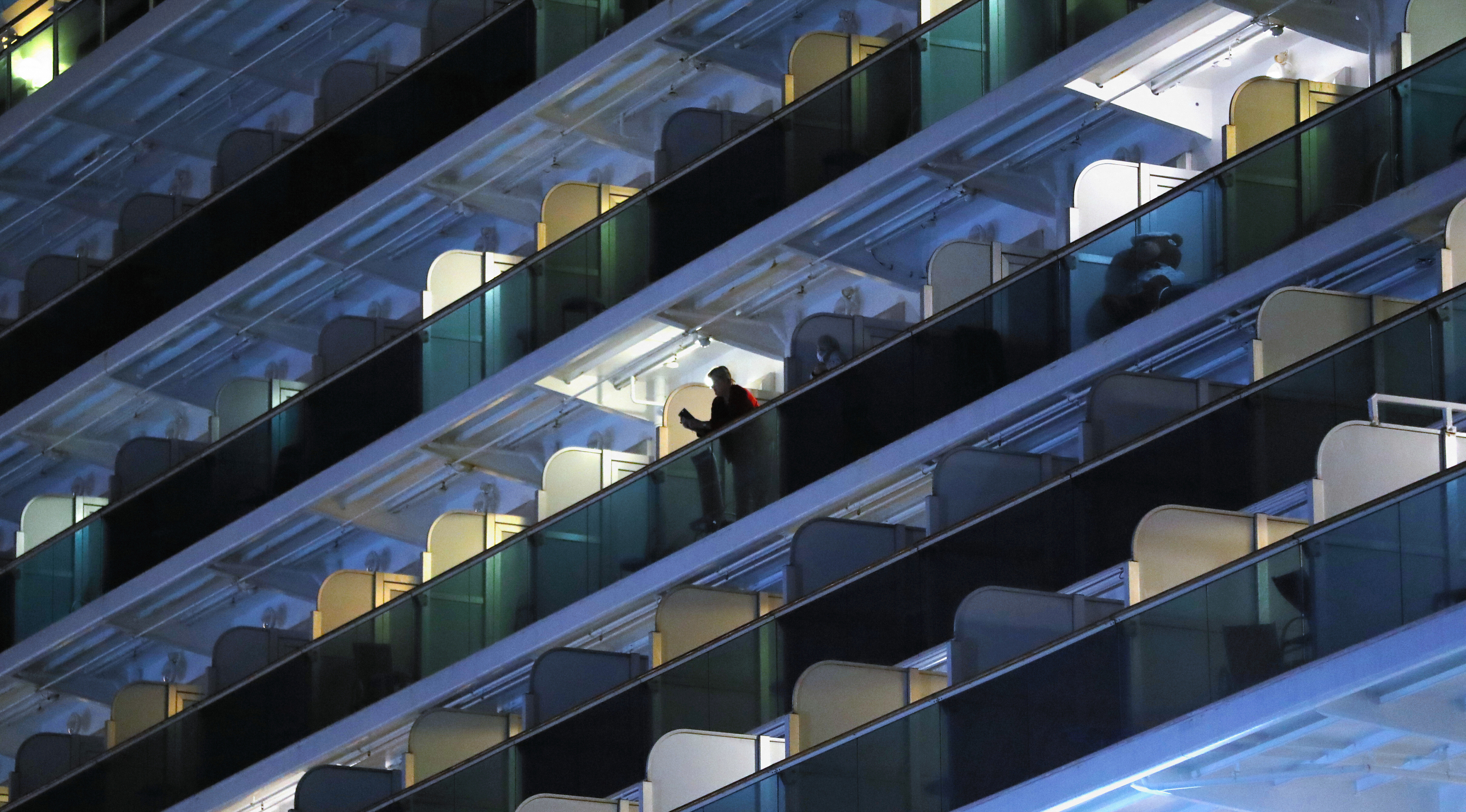 A passenger is seen at a balcony while clothes are hung on the Diamond Princess cruise ship on Friday.