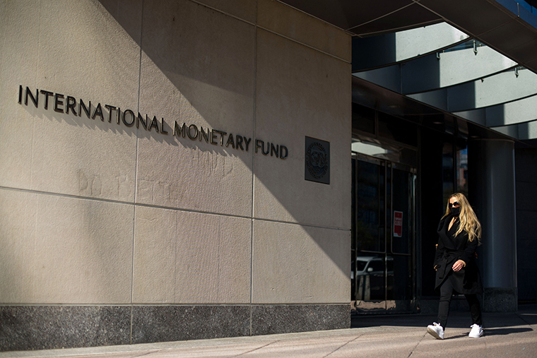 A woman walks past an International Monetary Fund headquarters (IMF) building in Washington, DC on April 5, 2021.