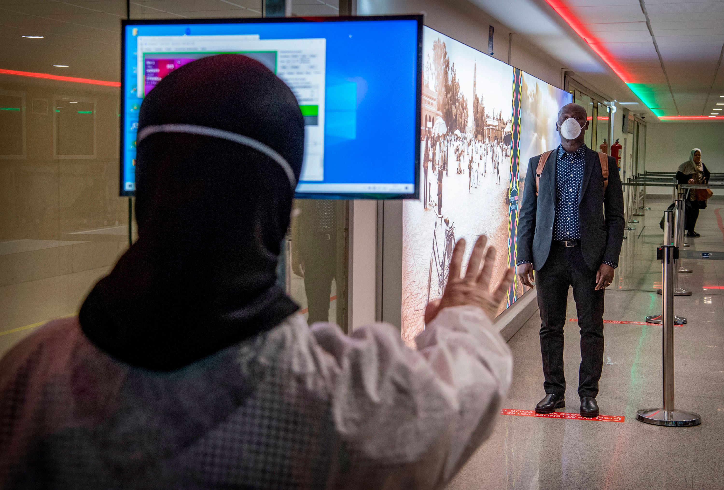 Moroccan health workers scan passengers arriving from Italy at Casablanca Mohammed V International Airport on March 3.