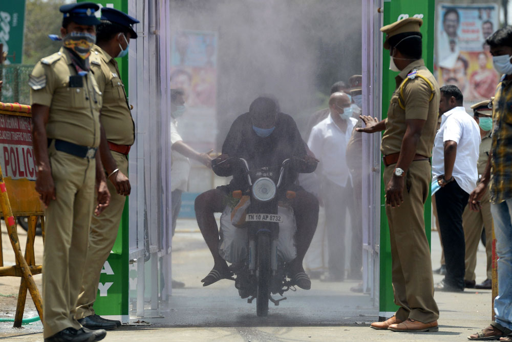 A motorist rides through a disinfection tunnel in Chennai, India, on April 5.