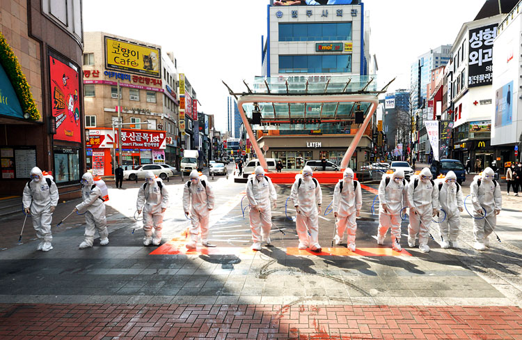 South Korean army soldiers wearing protective suits spray disinfectant to prevent the spread of coronavirus on a street in Daegu, South Korea, on Thursday, February 27.