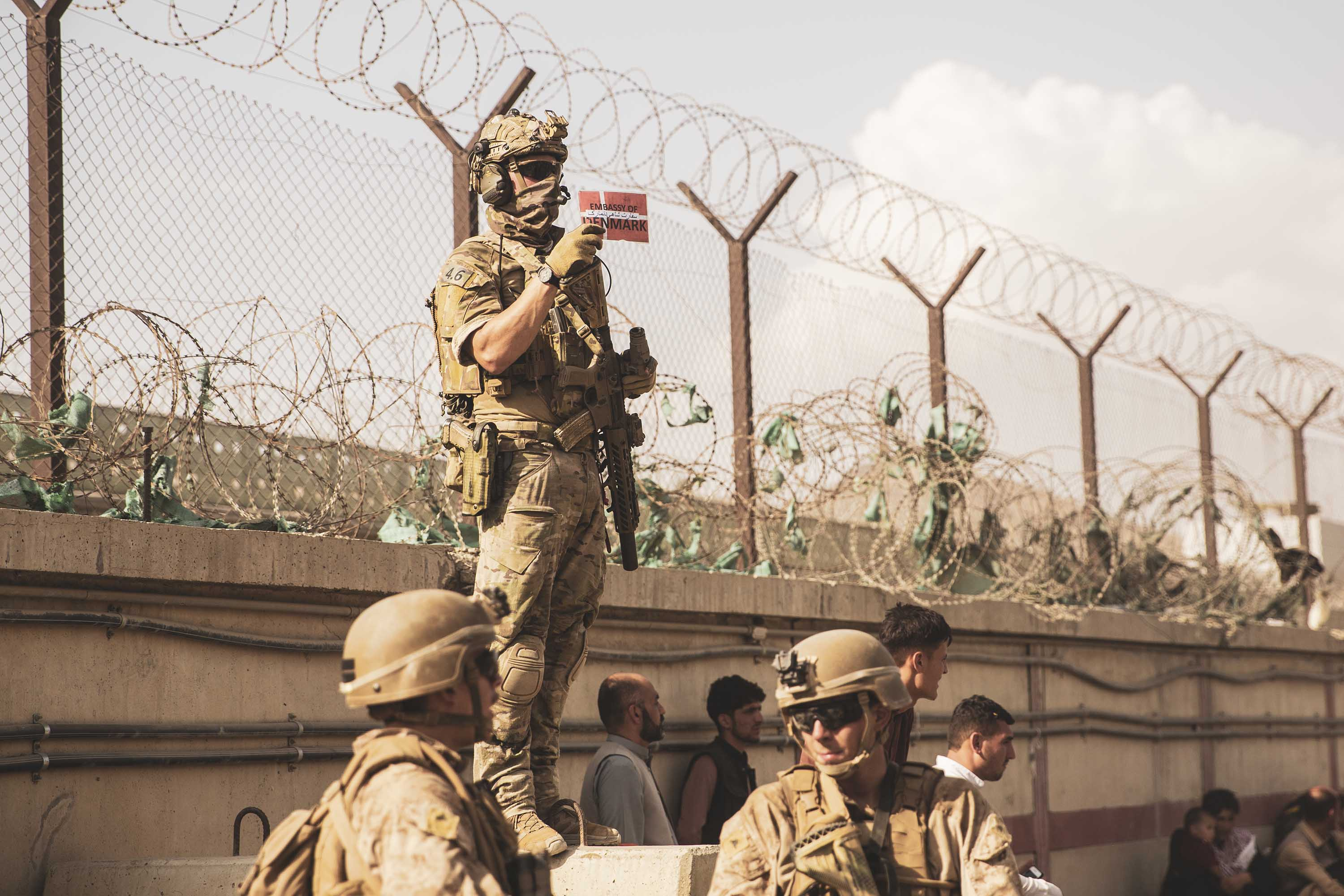 A Danish coalition service member holds up a sign with a Danish flag to identify families for evacuation at Hamid Karzai International Airport on August 21.