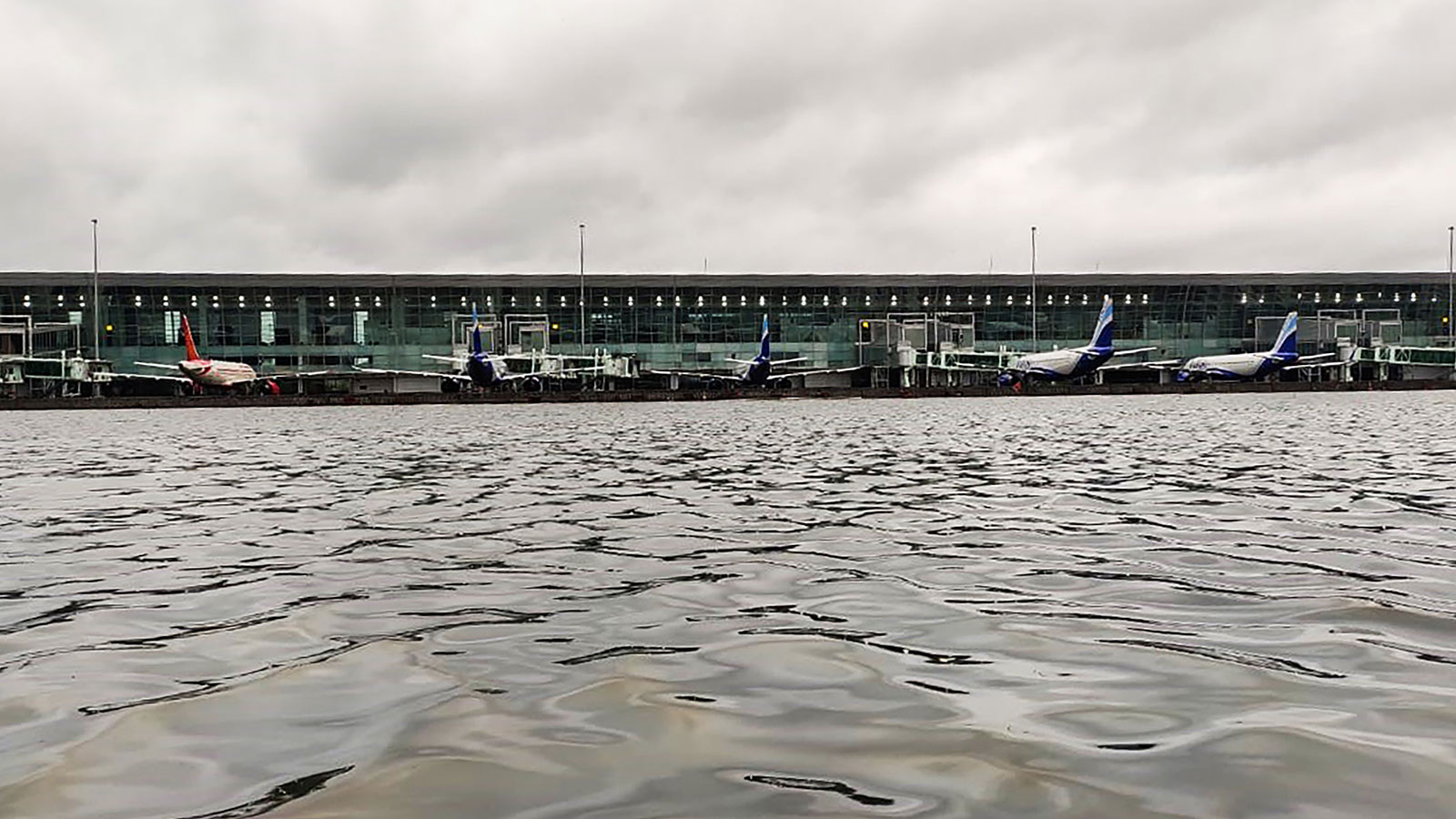 Aircrafts are parked at a terminal near the flooded tarmac at Netaji Subhas Chandra Bose International Airport after the landfall of Cyclone Amphan in Kolkata on May 21.