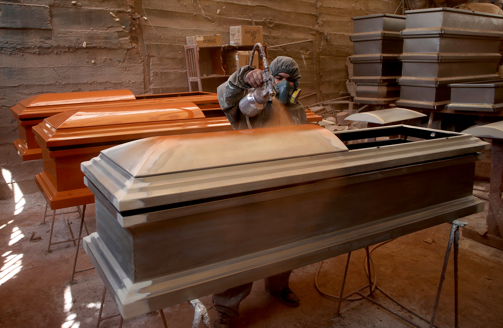 A factory worker applies the first coat of paint to a coffin in Lima, Peru, on May 29.