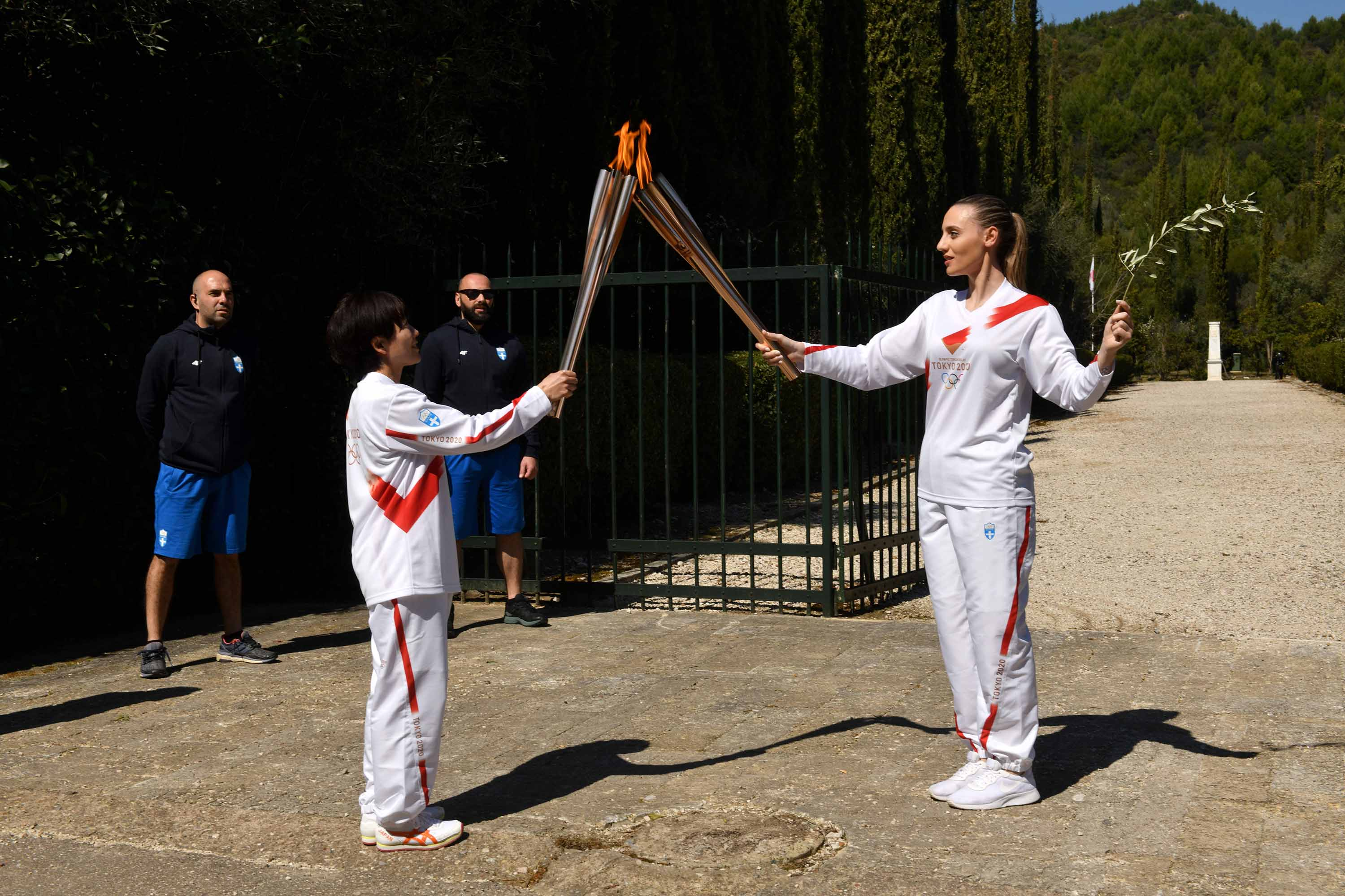 Torchbearer Anna Korakaki of Greece, right, passes the Olympic flame to Japan's Mizuki Noguchi during a lighting ceremony on March 12 in Olympia, Greece.