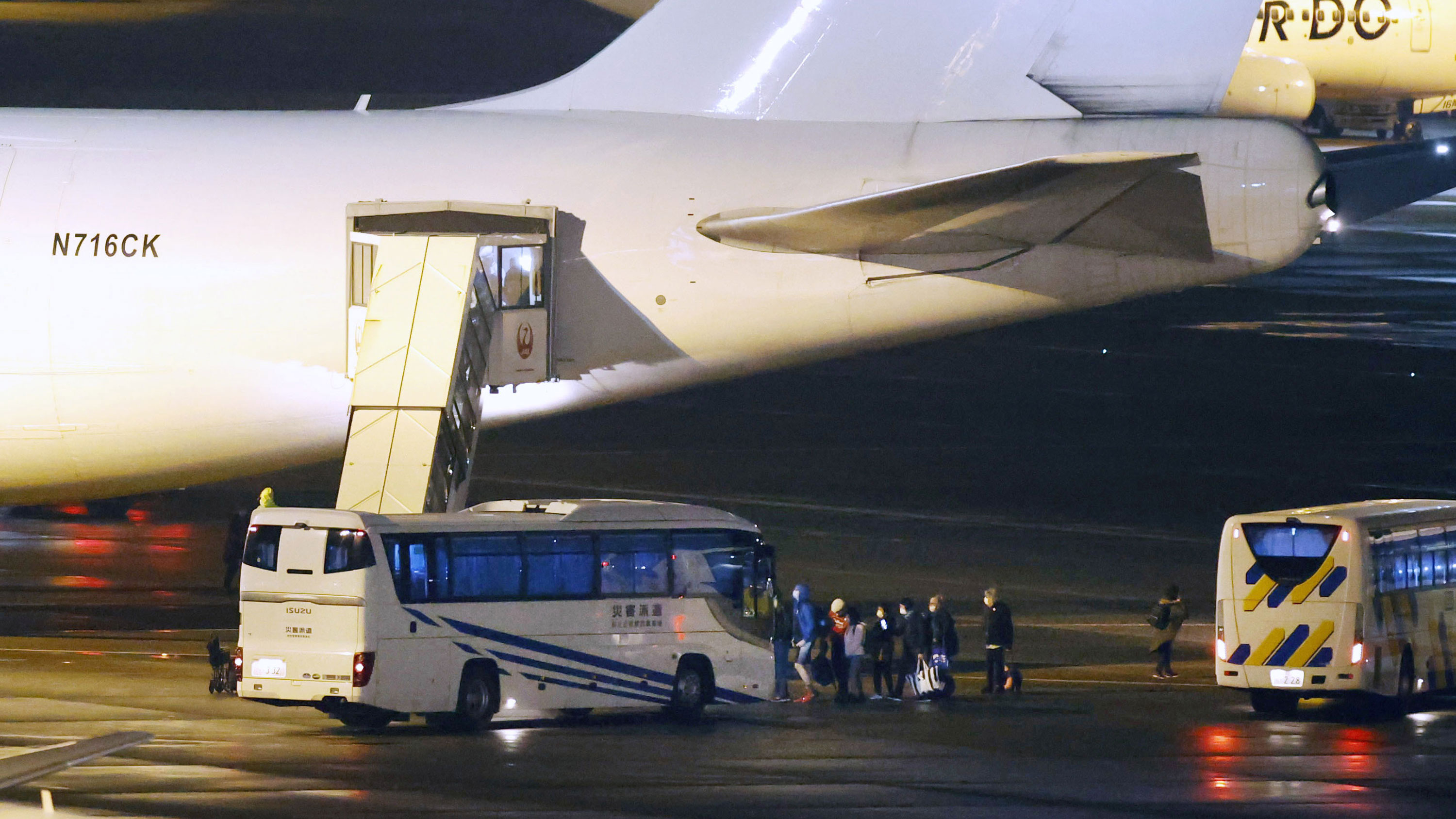 American citizens evacuated from the coronavirus-hit Diamond Princess cruise ship that has been kept in quarantine in Yokohama board a U.S. government-chartered plane at Tokyo's Haneda airport on Monday, February 17.