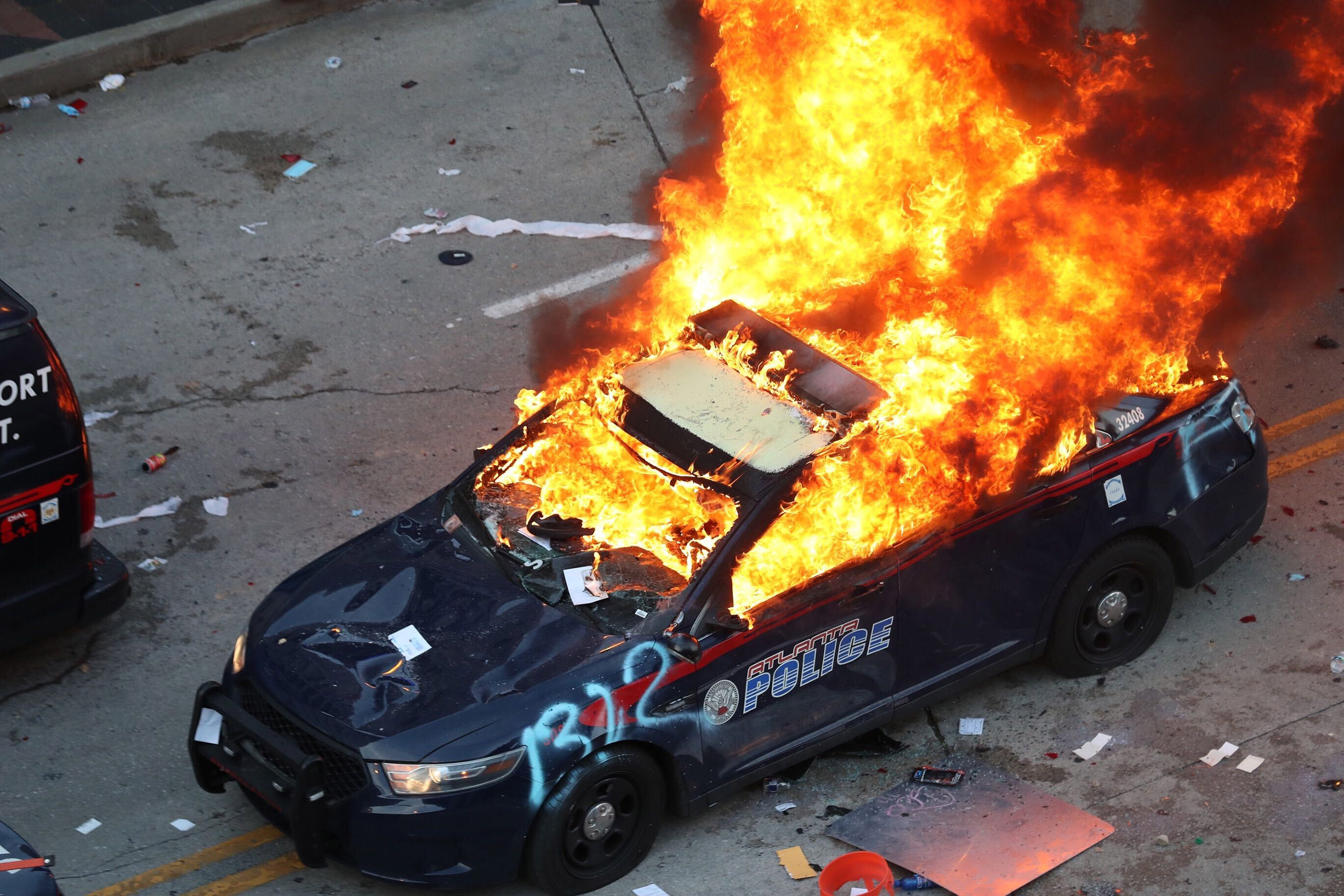 A police car burns after protesters marched to the Georgia State Capitol and returned to the area around the Centennial Olympic Park and CNN center in Atlanta, Gerpon Friday, May 29.