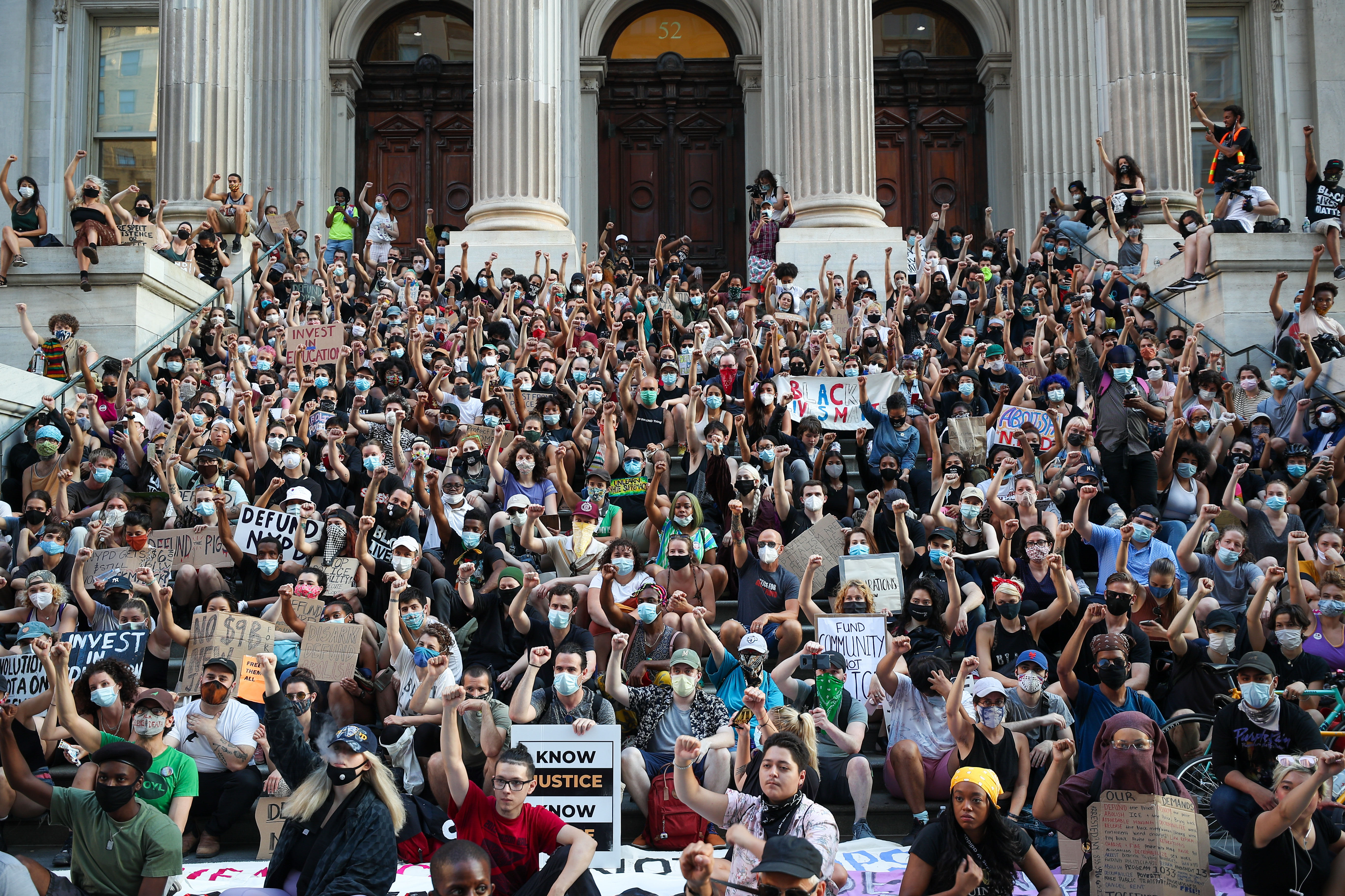 People sit by Tweed Courthouse, near New York City Hall, during an anti-racist protest on June 23.