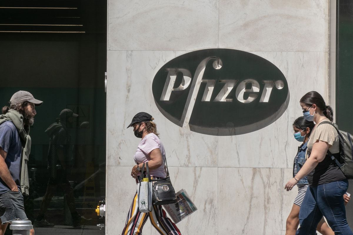 Pedestrians wearing protective masks walk past Pfizer Inc. headquarters on July 22 in New York City, New York.