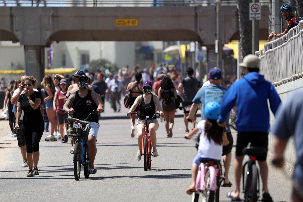 People ride and walk on a path along the beach amid the coronavirus pandemic on May 15 in Huntington Beach, California.
