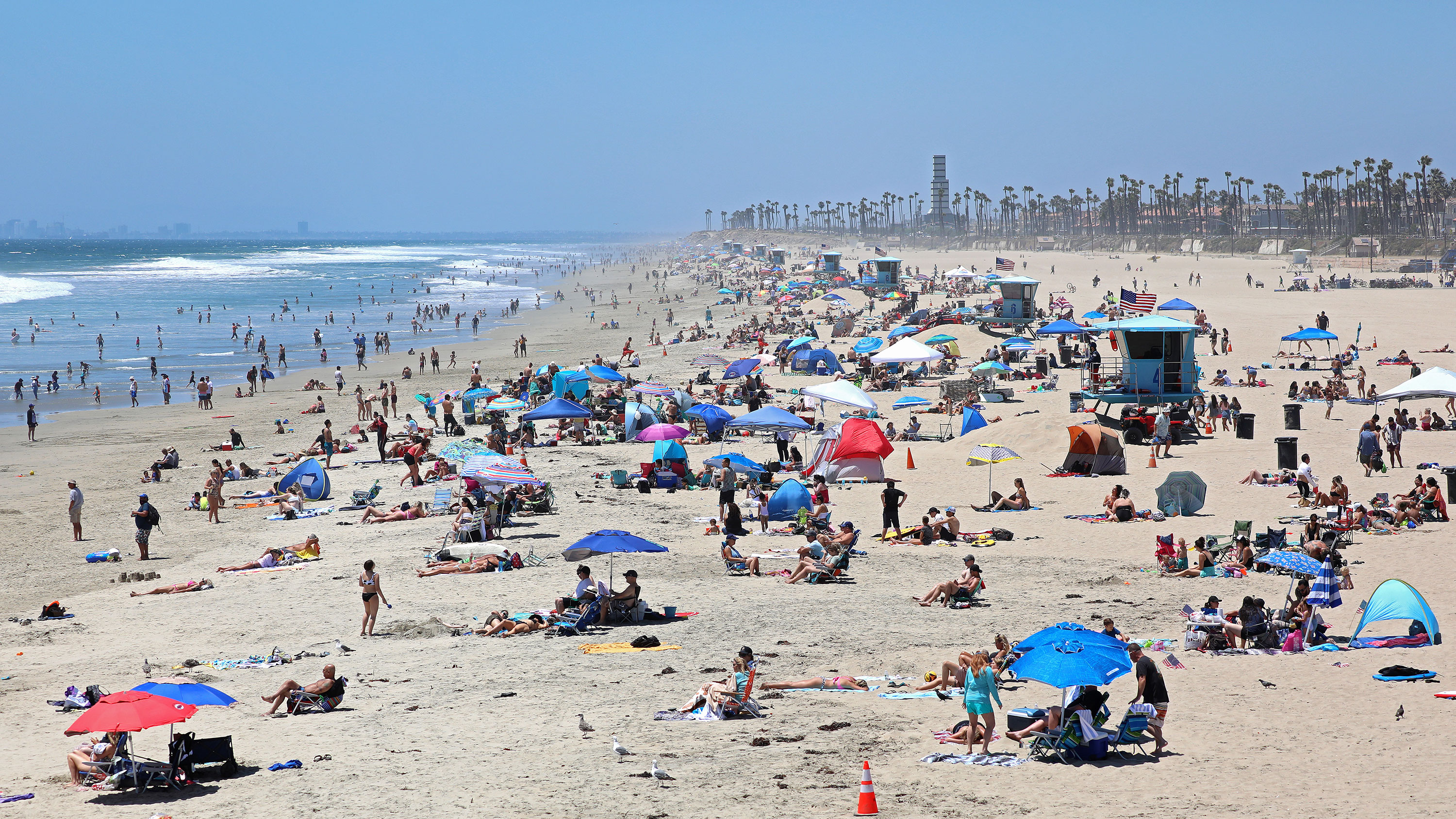 People gather at the beach on July 3 in Huntington Beach, California.