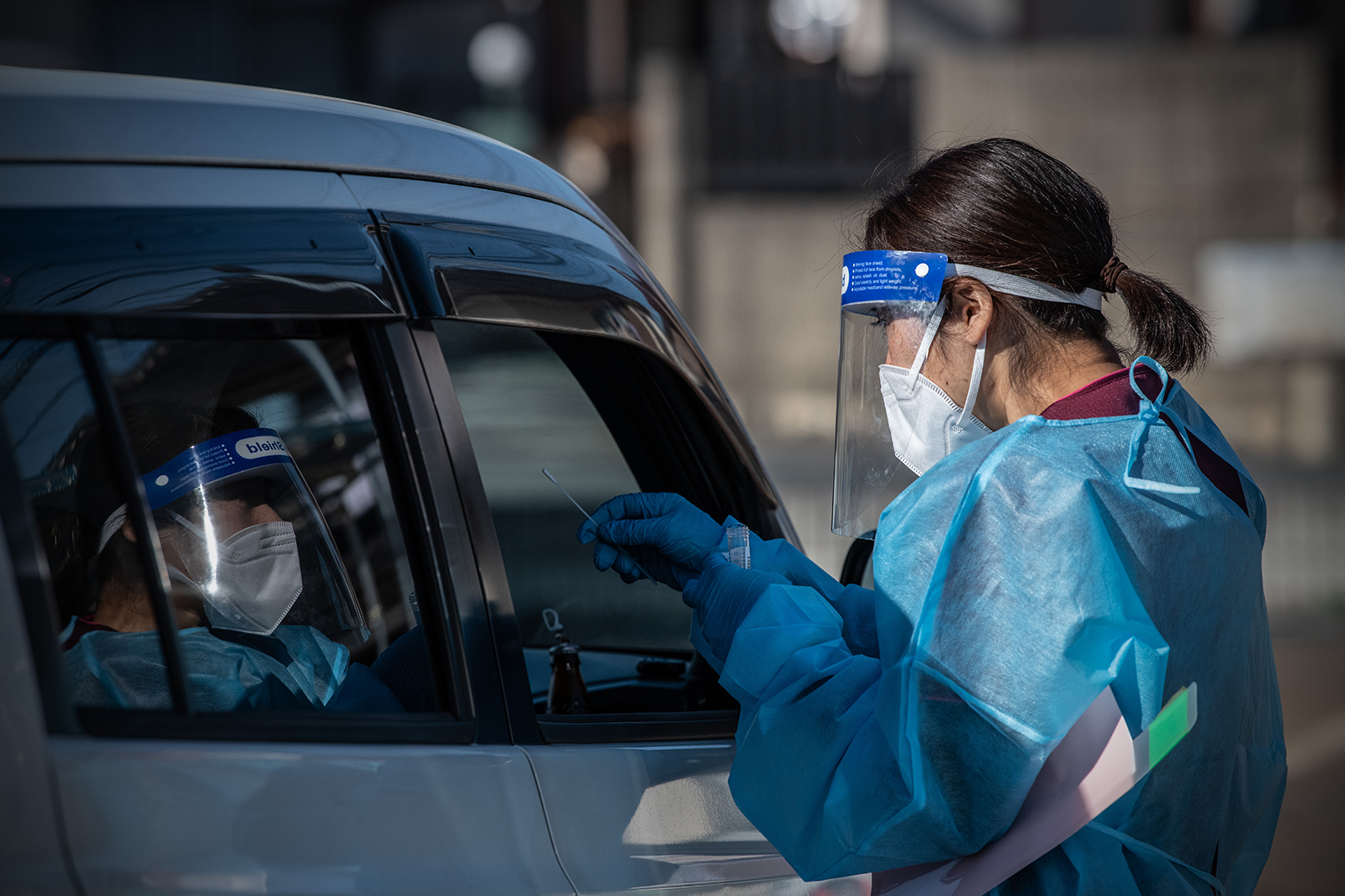 A nurse collects a nasal swab sample from a car driver at a Covid-19 PCR testing center at Fujimino Emergency Hospital in Miyoshi-machi, Japan, on December 18.