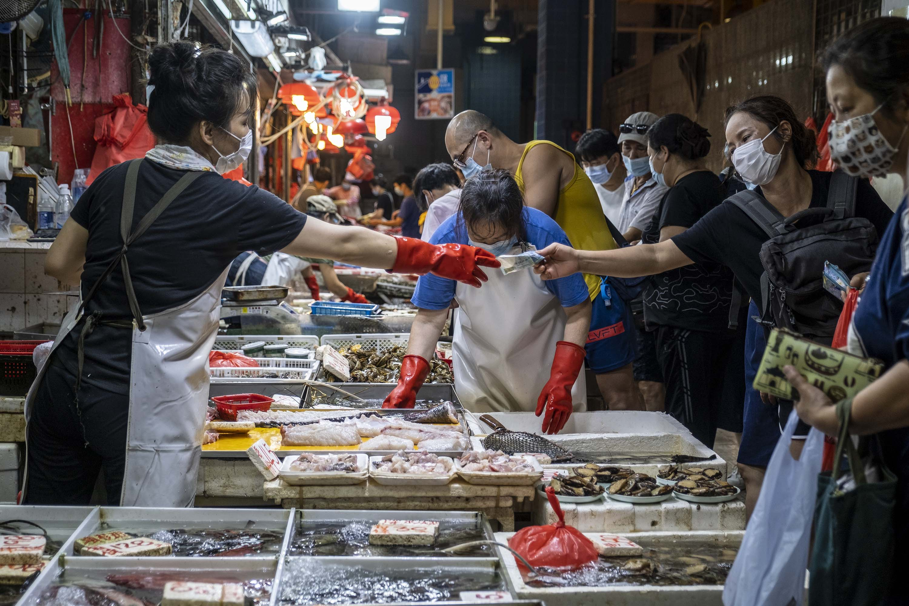 People are seen wearing face masks at a wet market Hong Kong on Saturday, July 25.