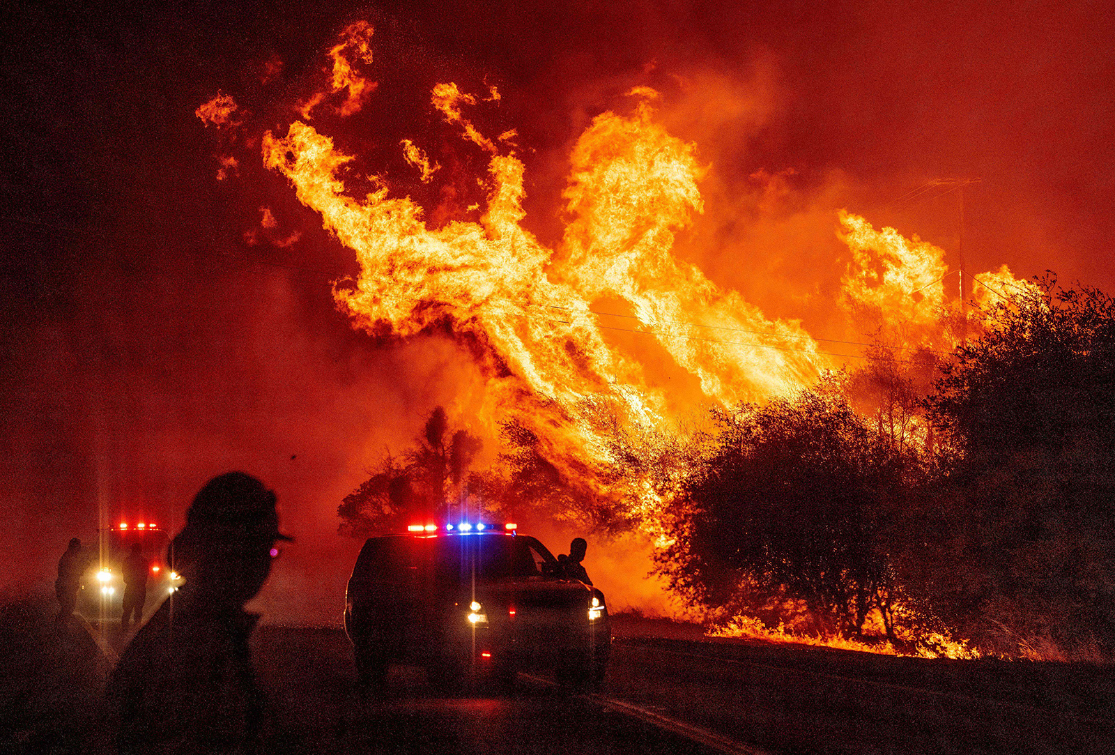 A law enforcement officer watches flames launch into the air as fire continues to spread at the Bear fire in Oroville, California on September 9.