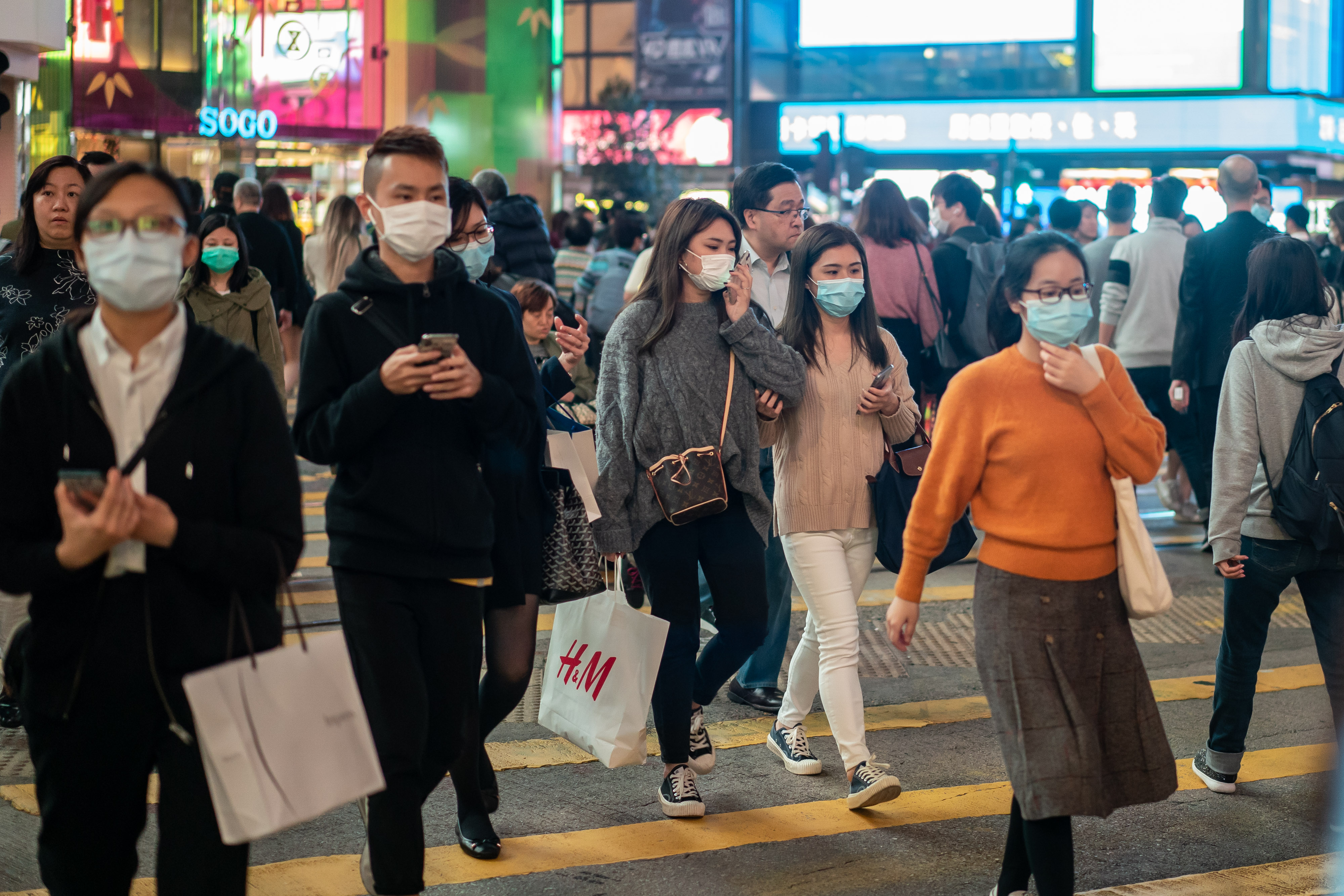 Pedestrians wear face masks as they walk through a crosswalk in Causeway Bay on January 23, 2020 in Hong Kong.
