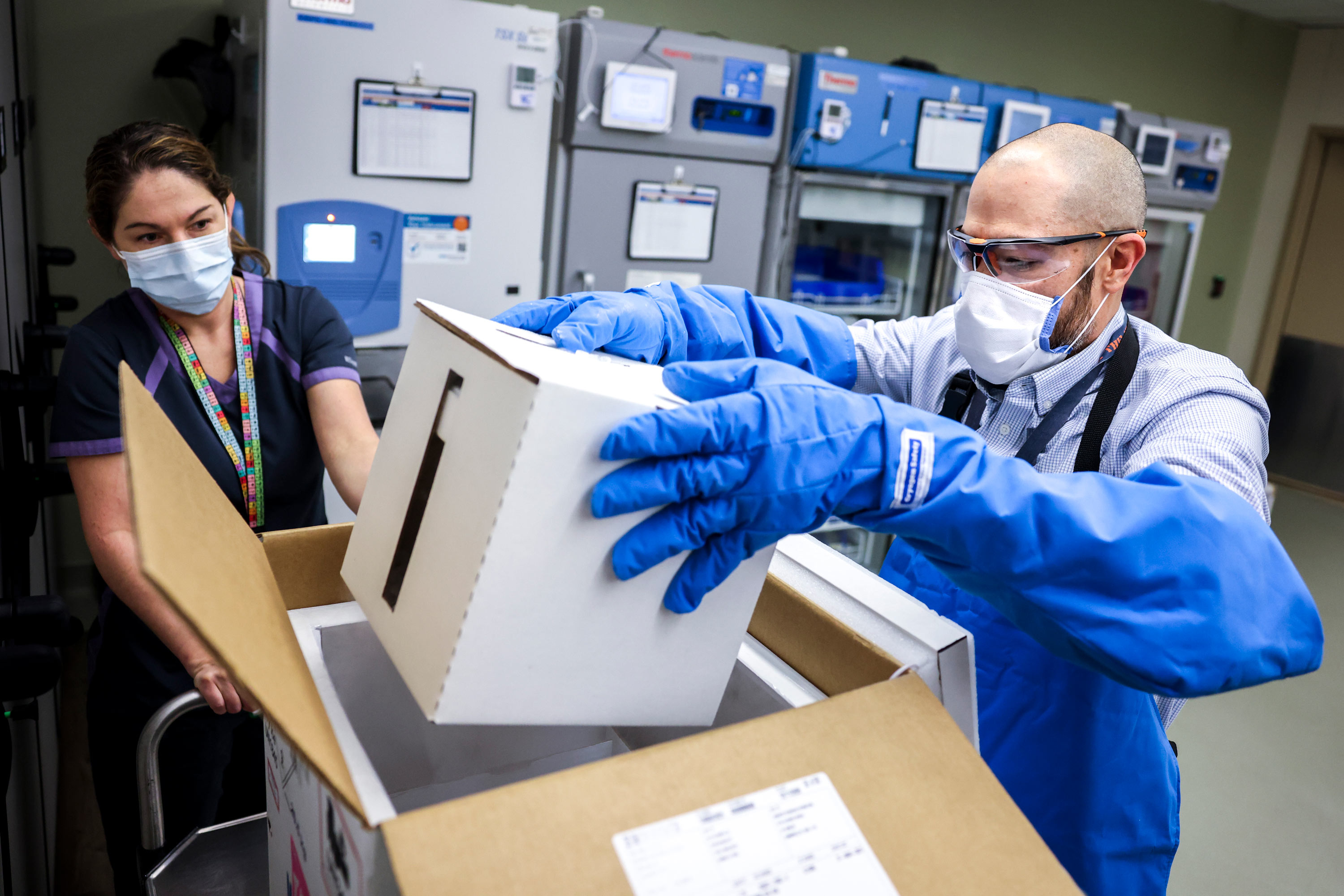 Rocky Mountain Regional VA Medical Center associate chief of pharmacy operations Terrence Wong opens a box containing a shipment of the Pfizer-BioNTech COVID-19 vaccine on December 15, 2020 in Aurora, Colorado.