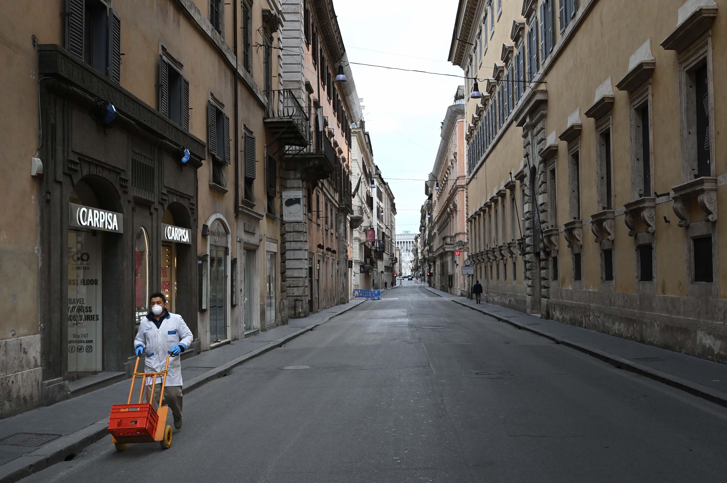 A delivery man wearing a protective mask pushes a cart across a deserted shopping street in Rome, Italy, on March 12.