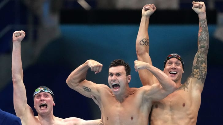 United States men's 4x100m freestyle relay team Bowen Becker, Blake Pieroni and Caeleb Dressel celebrate after winning the gold medal at the 2020 Summer Olympics on Monday, July 26, 2021, in Tokyo, Japan. Dressel has a full sleeve on his left arm, while Pieroni sports the Olympic rings.