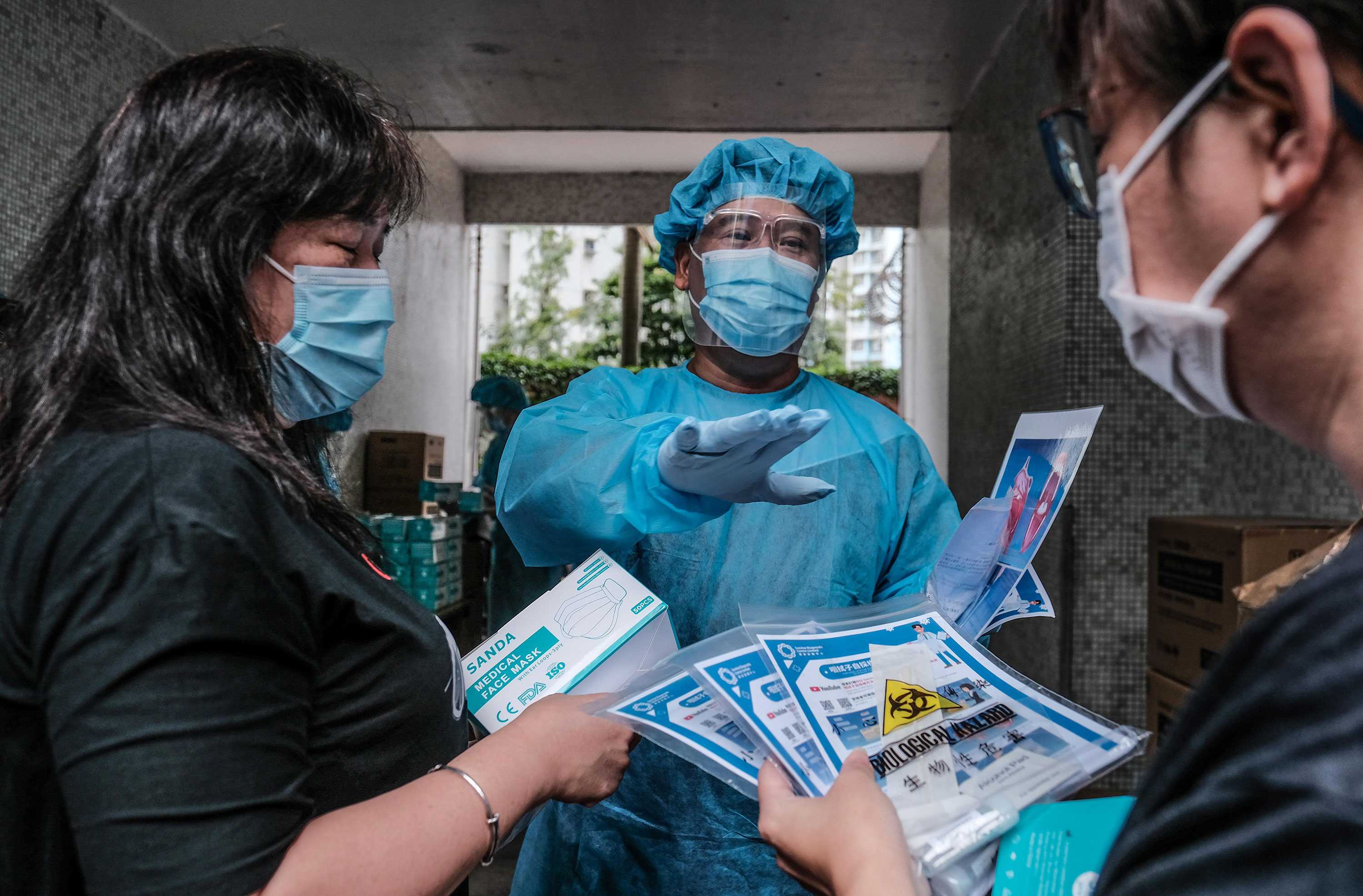 Medical workers hand out coronavirus test kits to local residents on August 7 in Hong Kong.