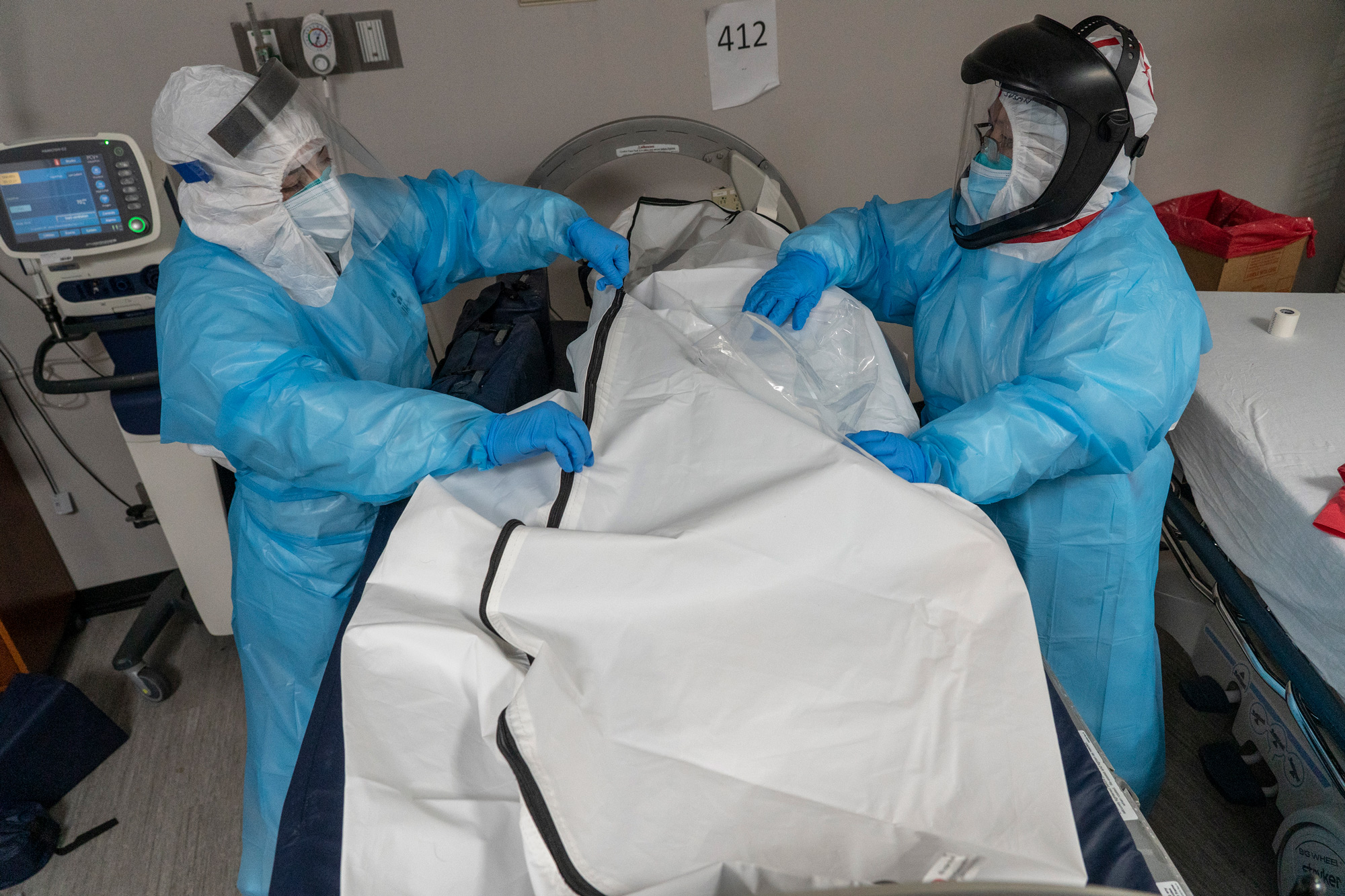 Medical staff members zip up a body bag containing a deceased patient in the COVID-19 intensive care unit at the United Memorial Medical Center on December 6 in Houston, Texas.