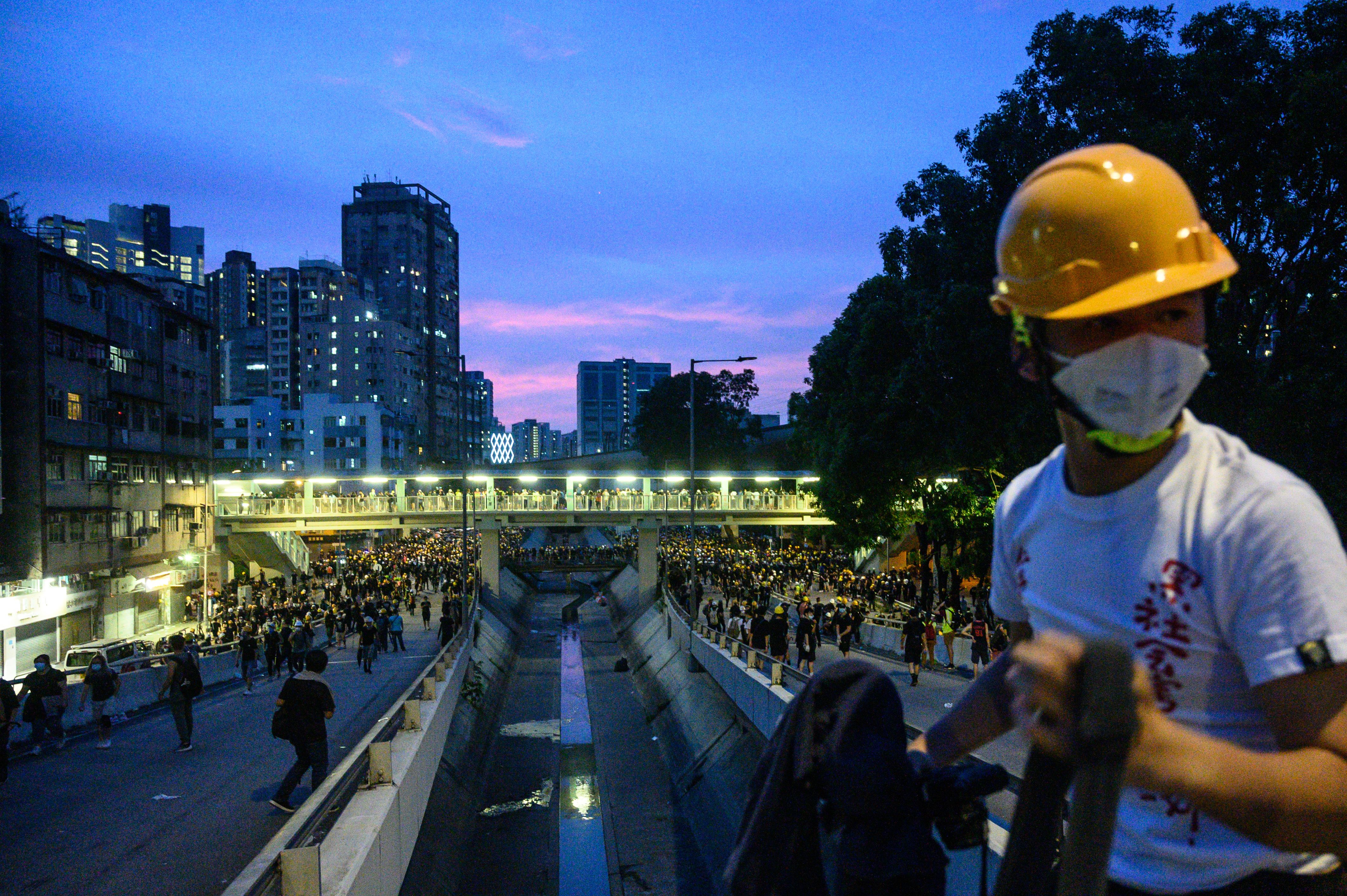 Protesters walk on a bridge as they move back to Yuen Long MTR station on Saturday.