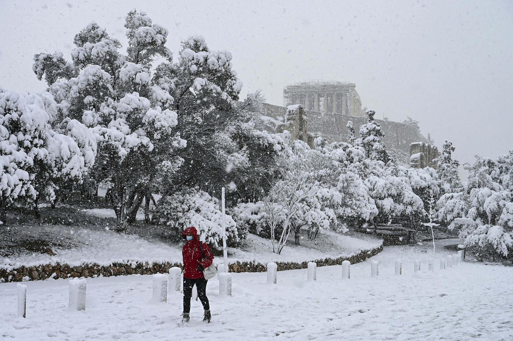 A woman walks past the Parthenon temple during heavy snowfall in Athens, Greece, on February 16, 2021.