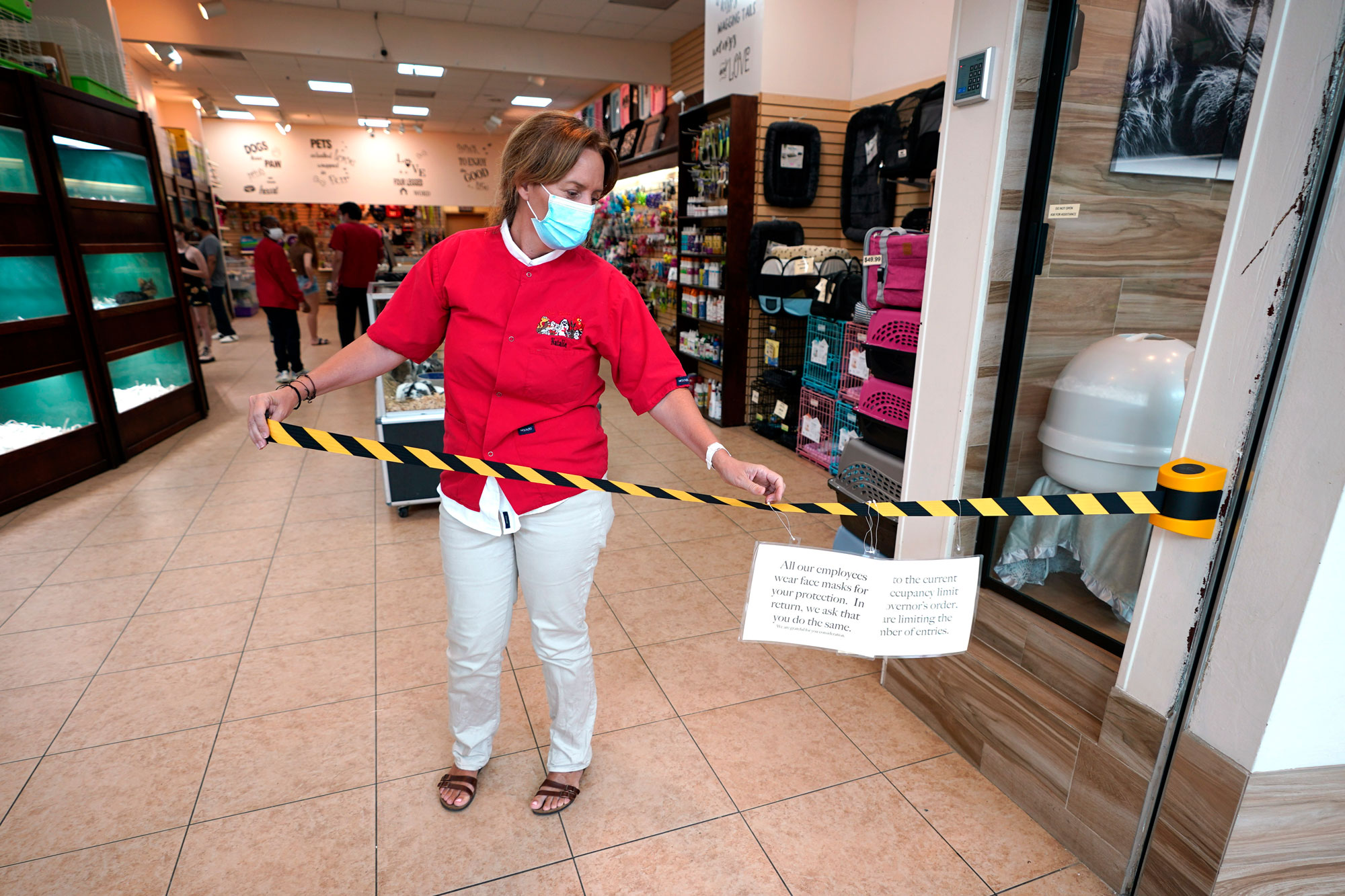 Store manager Natalie Hijazi temporarily closes off the entrance to a Pet Fair store inside The Woodlands Mall on Tuesday, May 5, in The Woodlands, Texas.