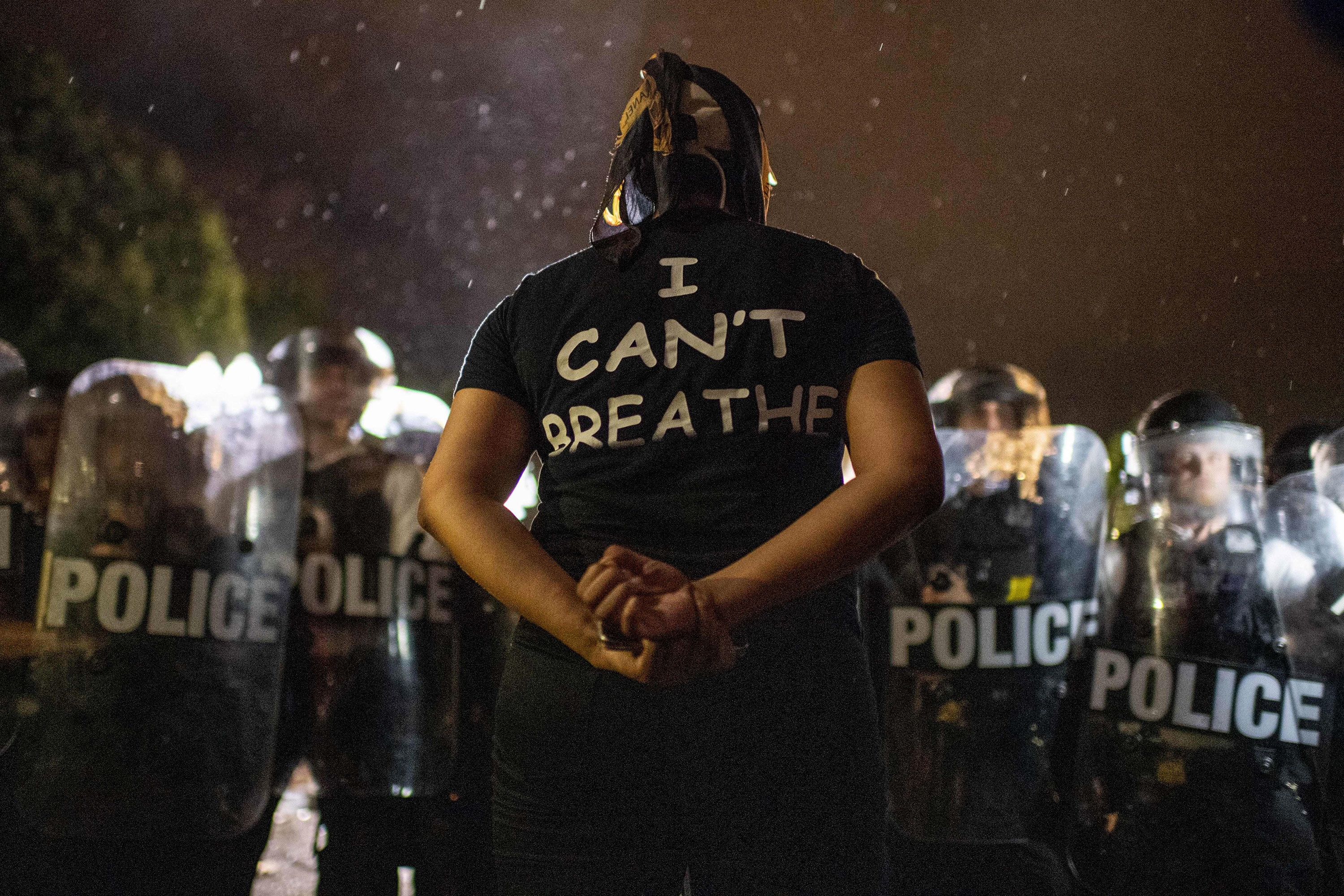 A protester stands in front of police outside the White House in Washington on May 30.