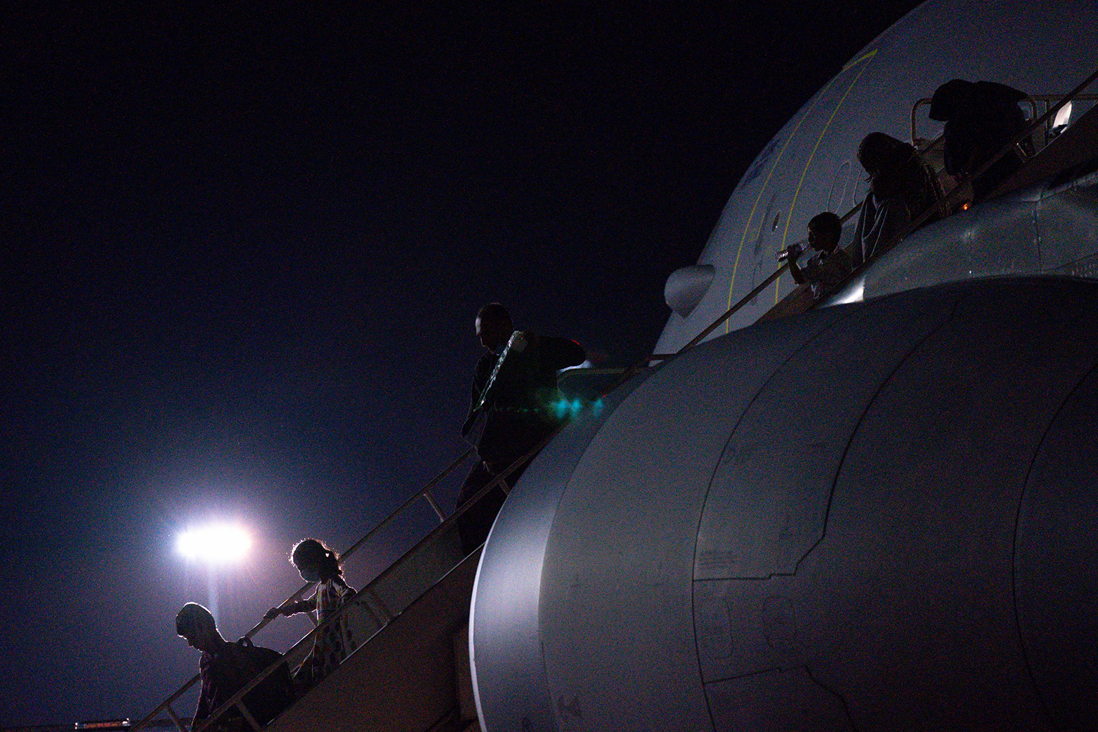 Passengers evacuated from Afghanistan disembark a British military transport aircraft at RAF Brize Norton station in southern England on August 26.