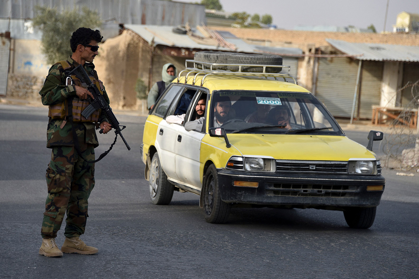 An Afghan security personnel stands guard along a road in Kandahar on July 14.