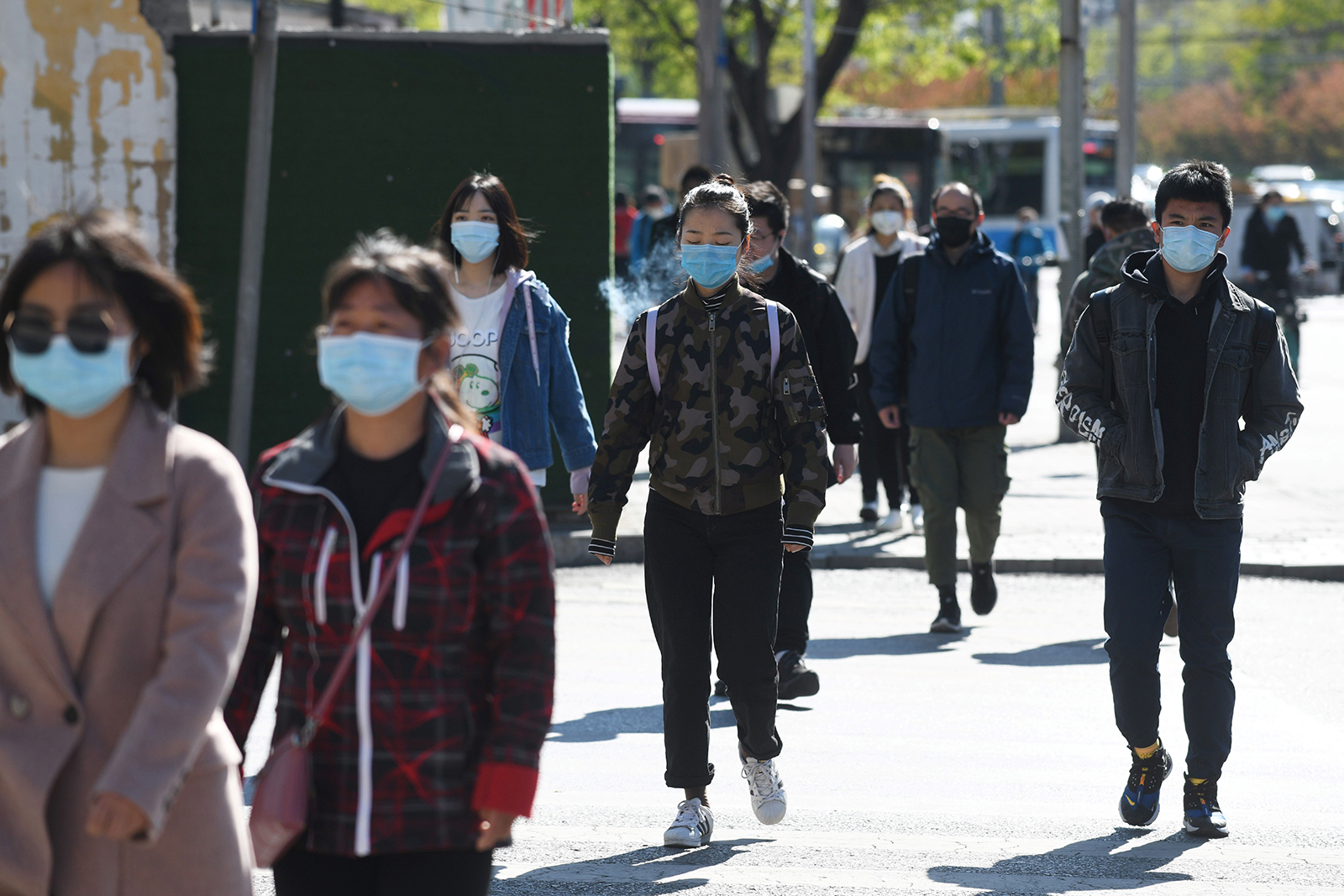 People wear face masks amid concerns of the coronavirus as they walk to a subway station in Beijing on April 23.