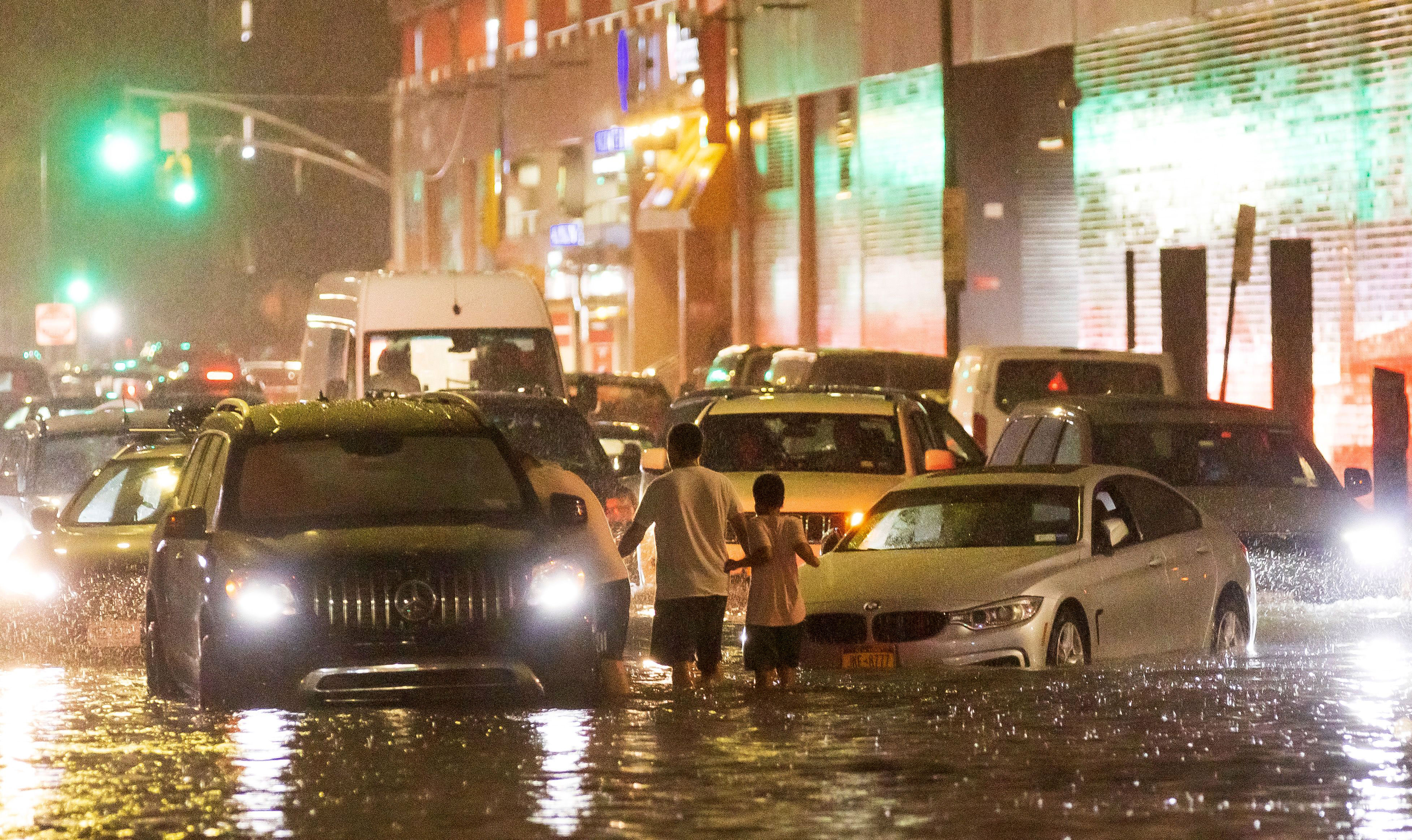 People and cars are on a street flooded by heavy rain in Queens, New York, on September 1.