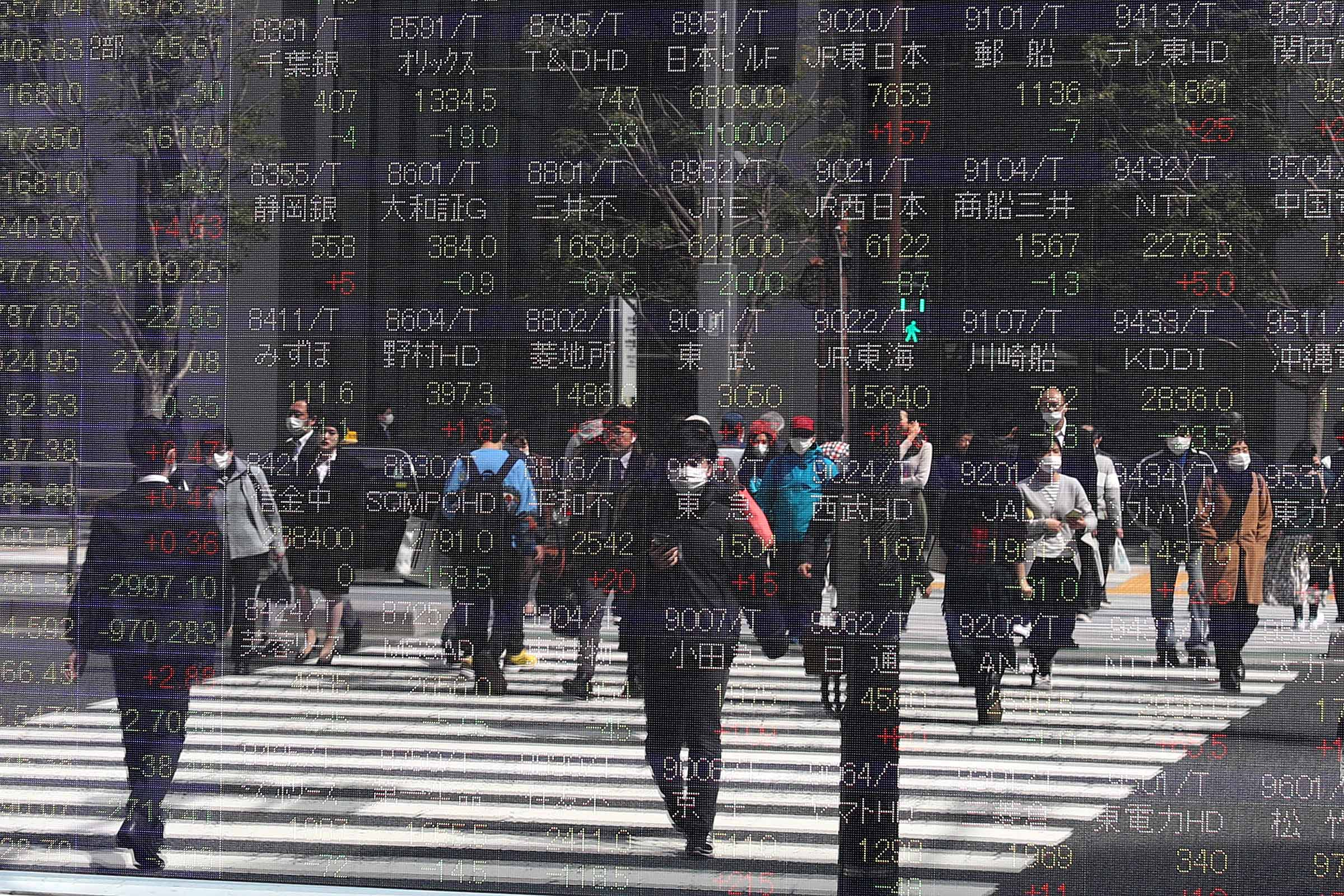 Electronic stock market displays reflect pedestrians in Tokyo, Japan, on March 16.