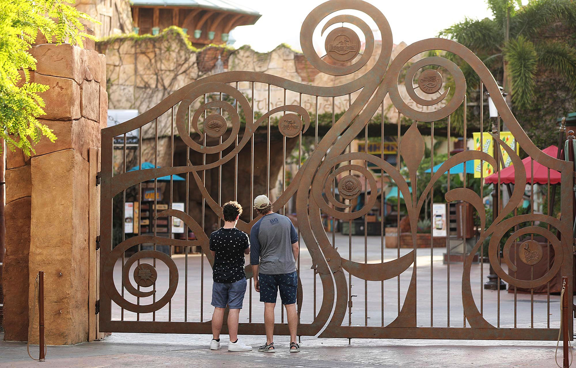 Guests peer through the closed gate to Universal's Islands of Adventure beside Universal CityWalk on May 14 in Orlando, Florida.